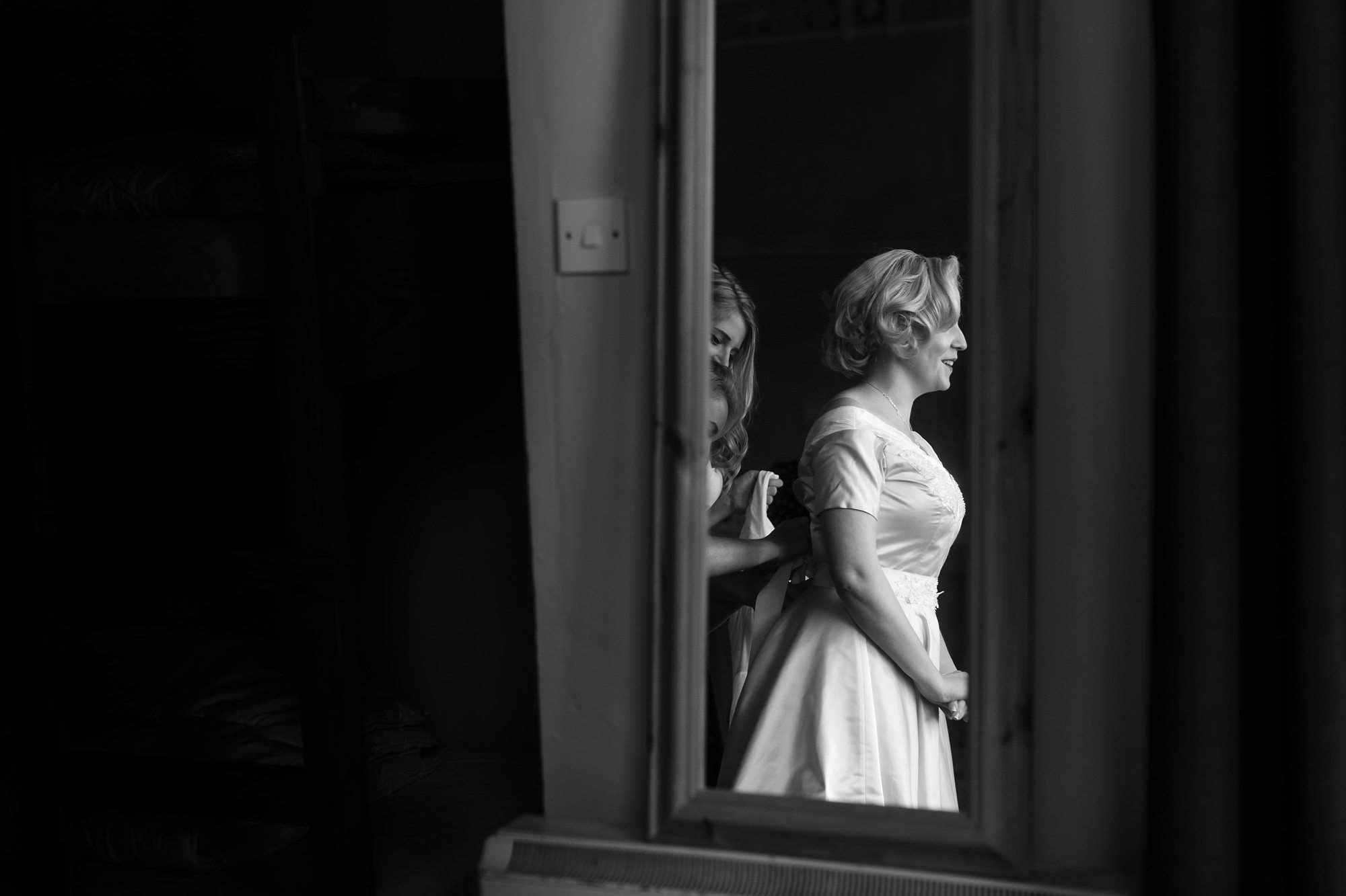 Reflection of bride being buttoned up in mirror Derwentwater Independent Hostel Wedding