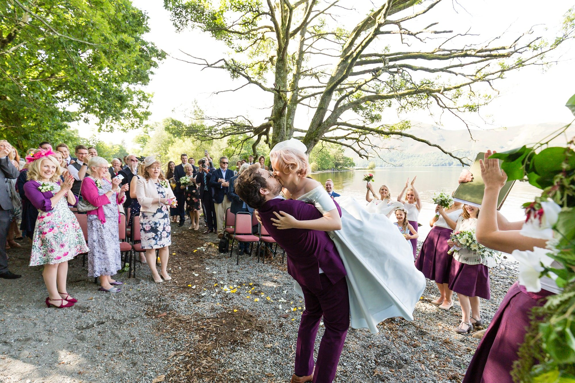 Groom picks up bride to kiss during the ceremony Derwentwater Independent Hostel Wedding