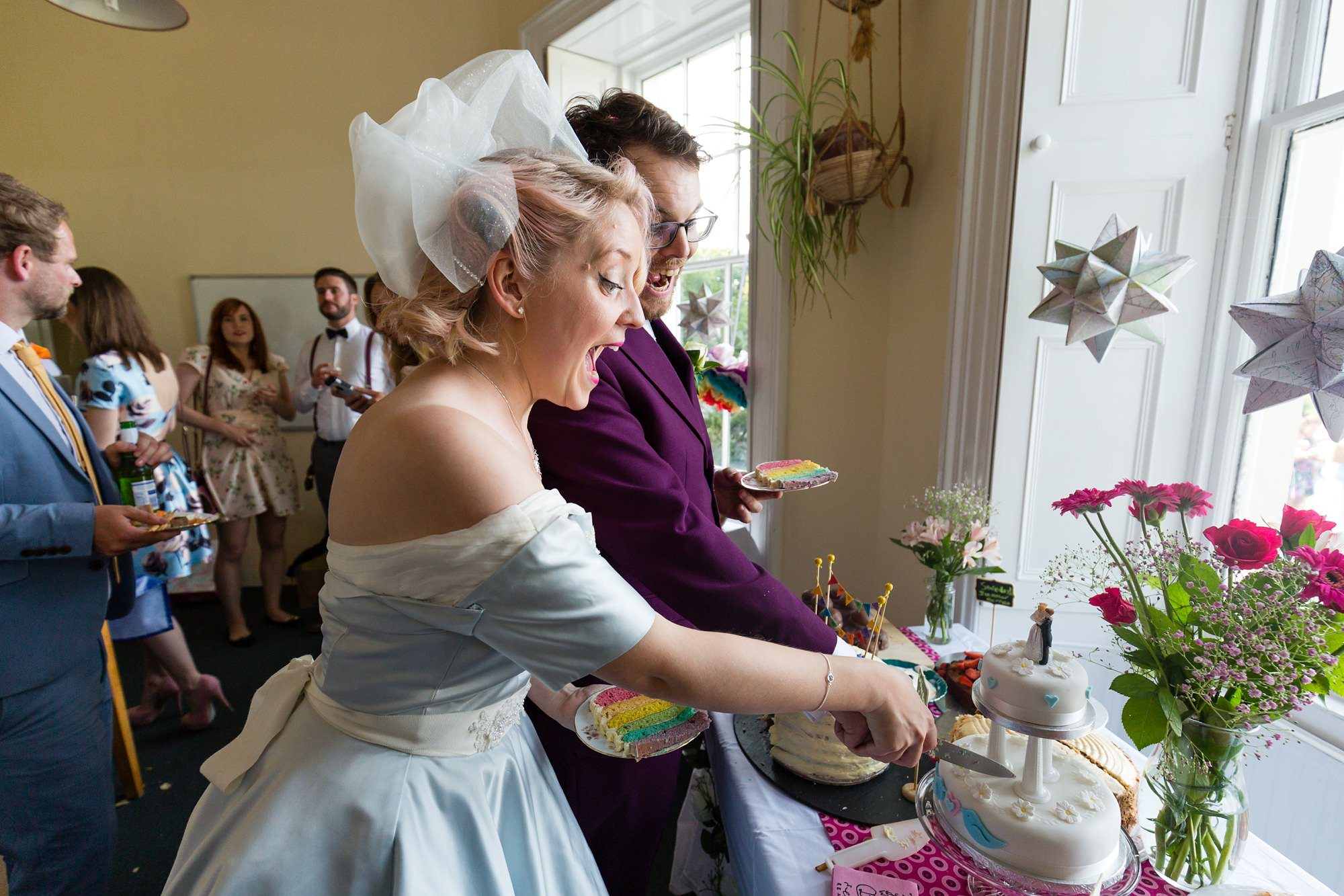 Bride in blue dress cutting the cake Derwentwater Independent Hostel Wedding
