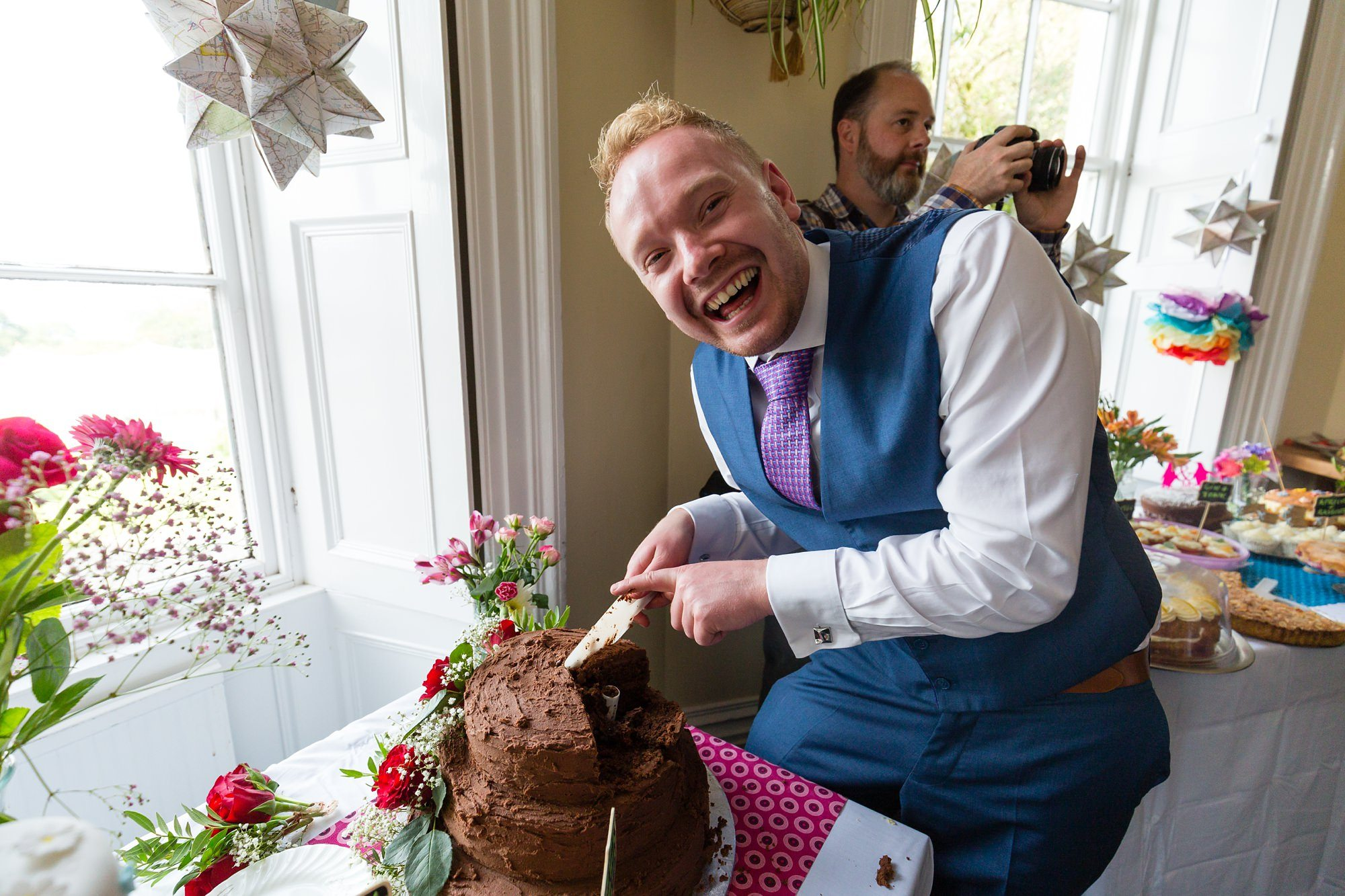 Laughing by the cake at Derwentwater Independent Hostel Wedding