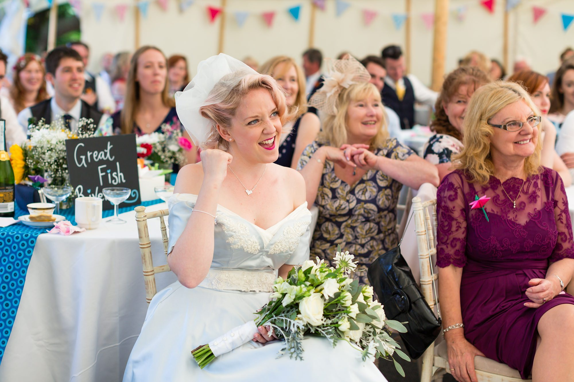 Bride in blue dress does fist pump Derwentwater Independent Hostel Wedding