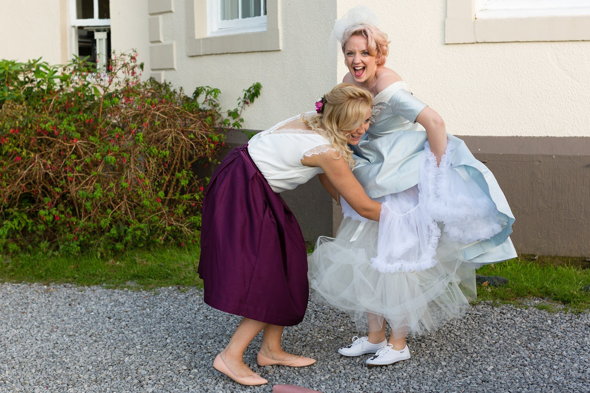Bridesmaid helps bride adjust petticoat