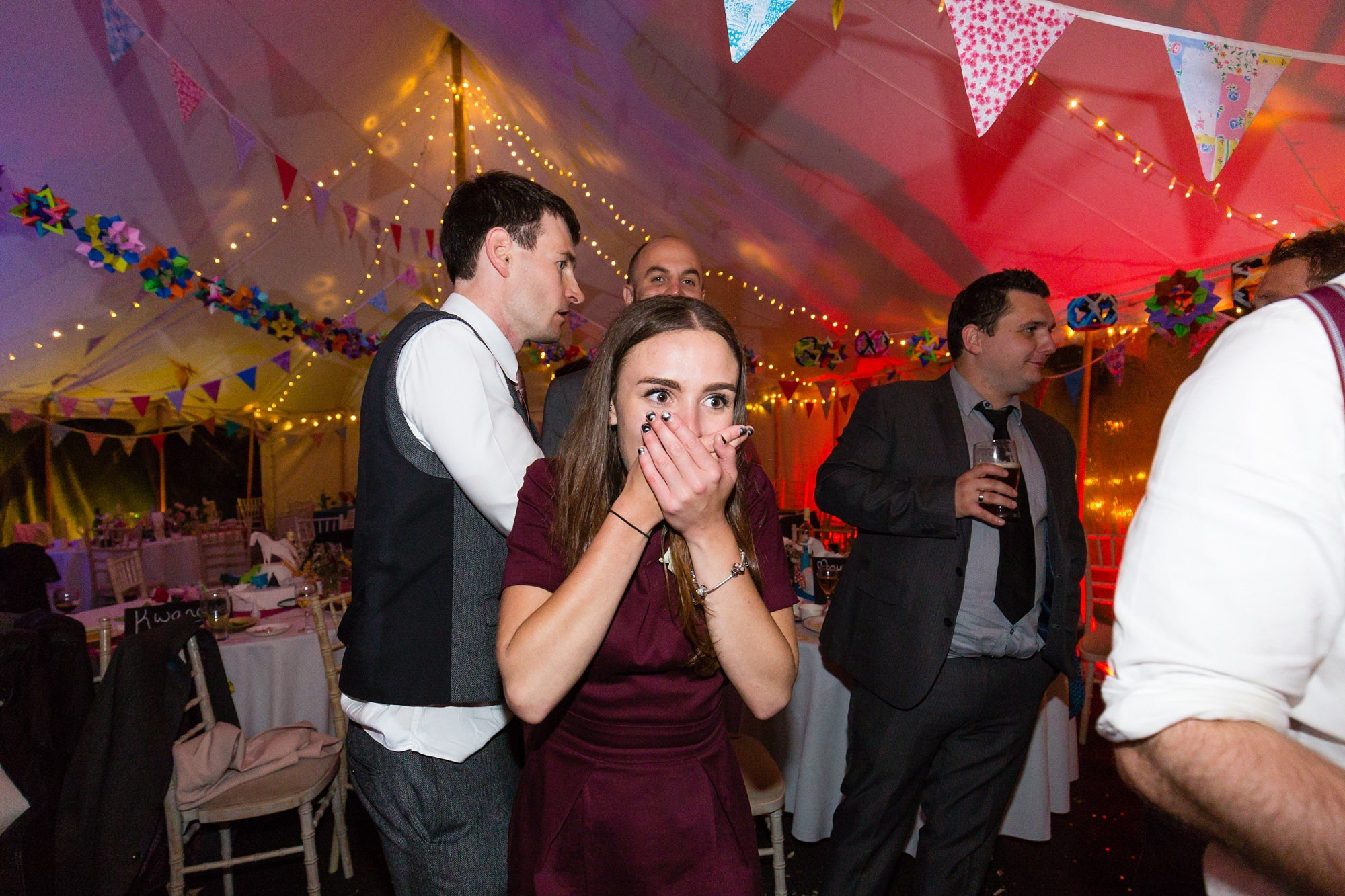 Guest laughs and covers face during the party Derwentwater Independent Hostel Wedding