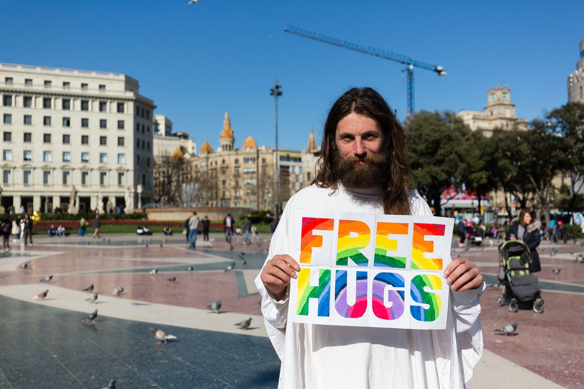 "Man holding rainbow sign that says "" Free Hugs"""