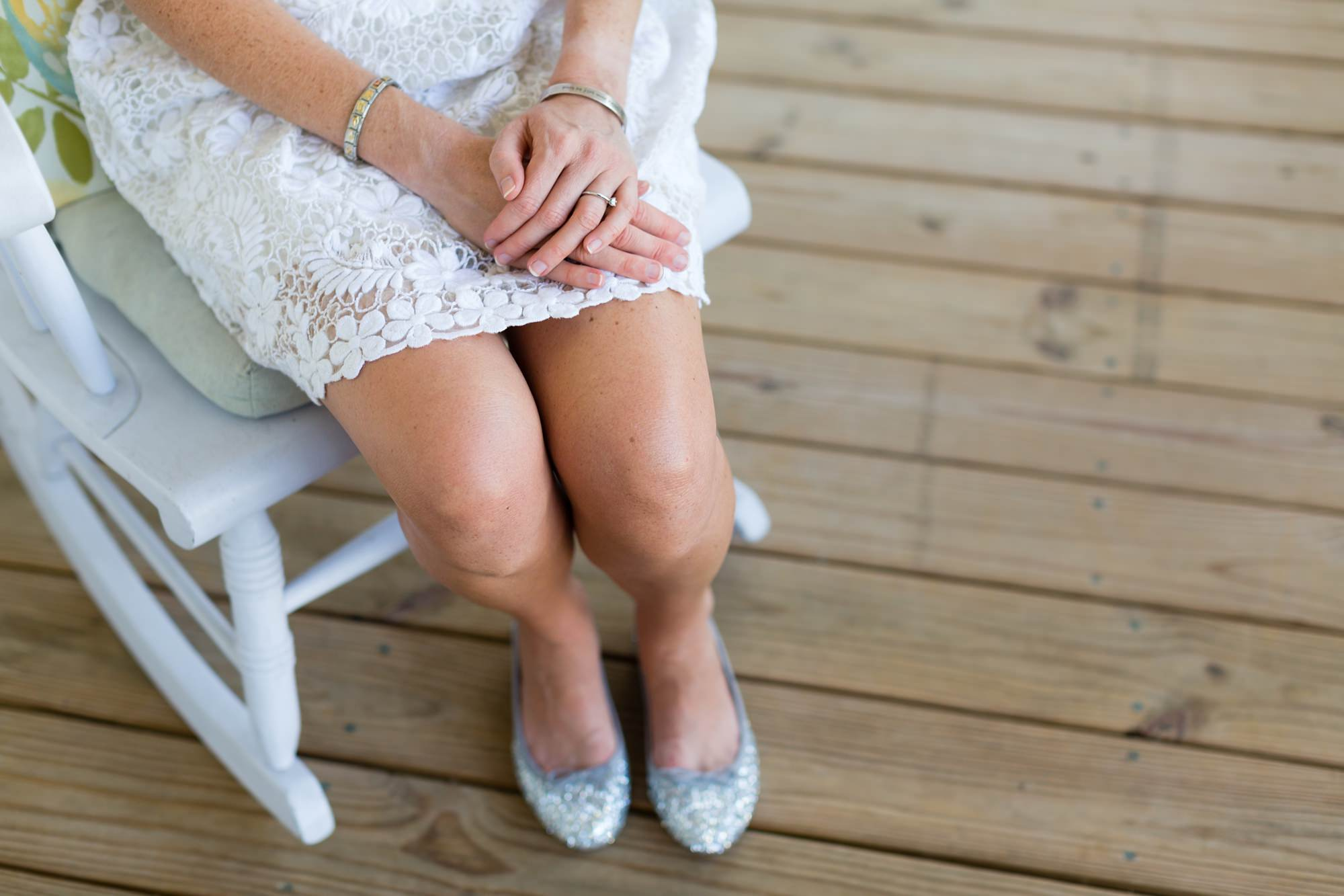 Detail of bride's hands and silver slippers