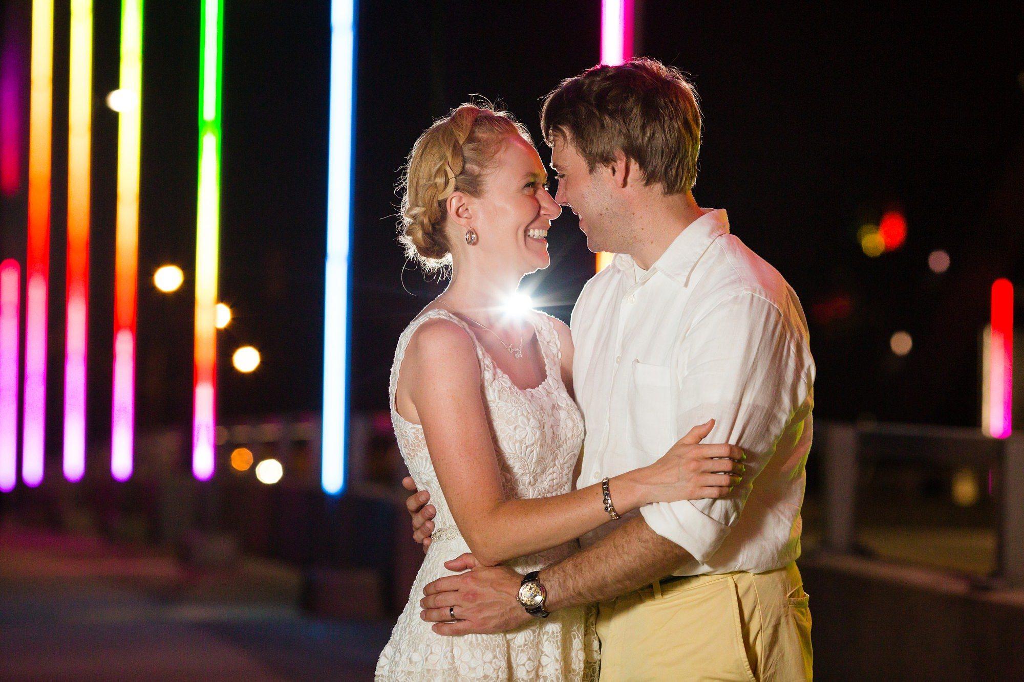 Brdie and groom on bridge with rainbow lights