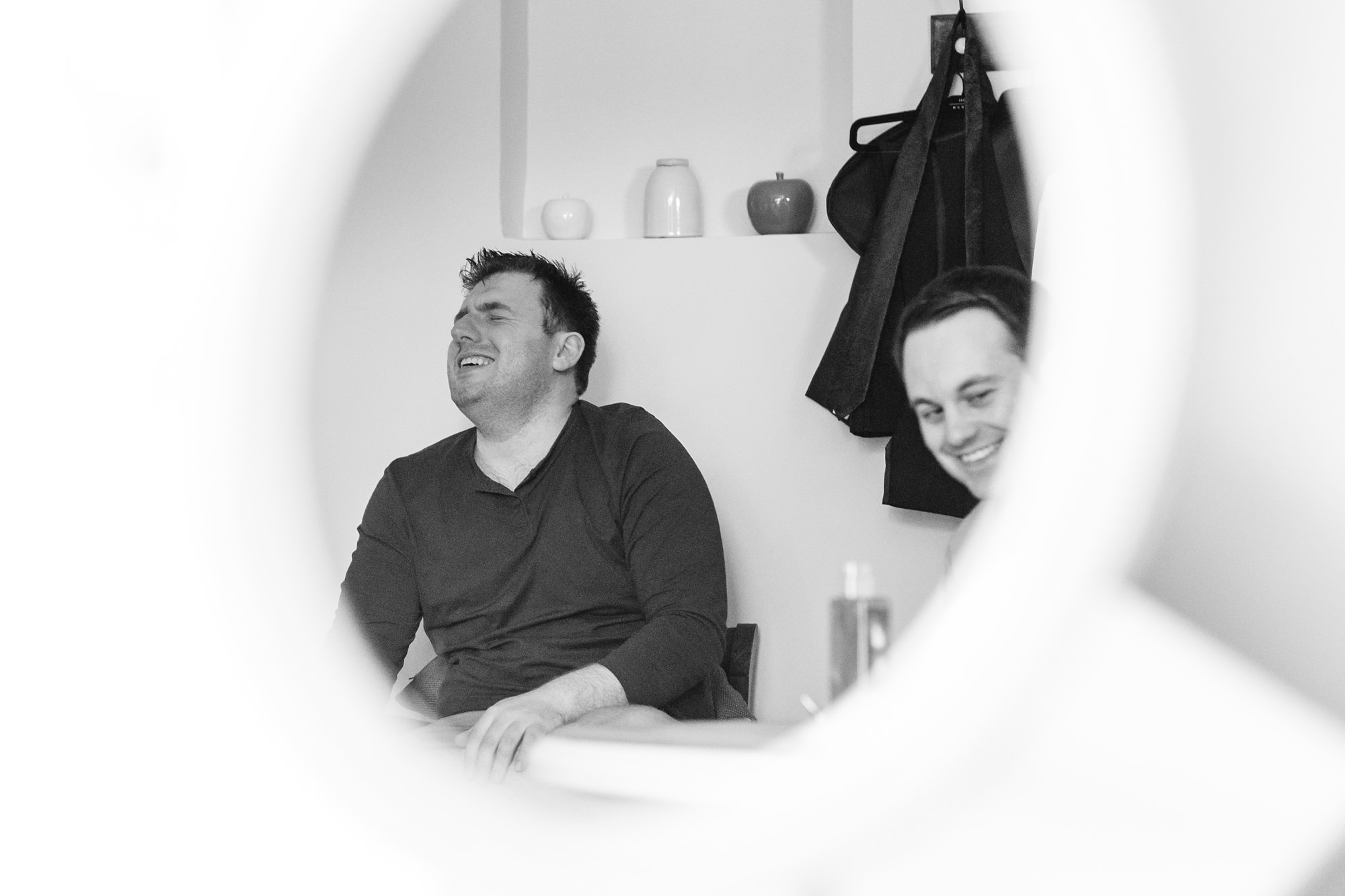 Reflection of groomsman laughing in mirror at York Wedding
