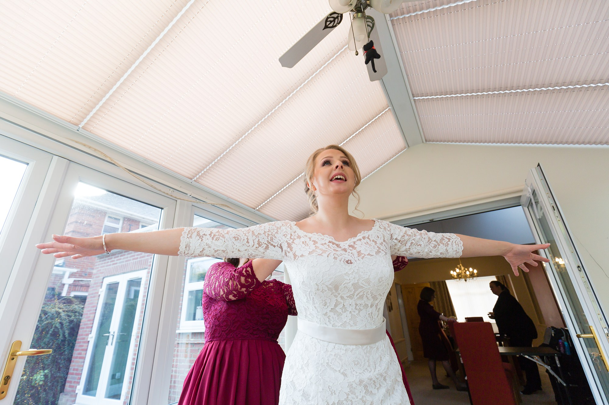 Bride getting into dress holding out arms at wedding in York