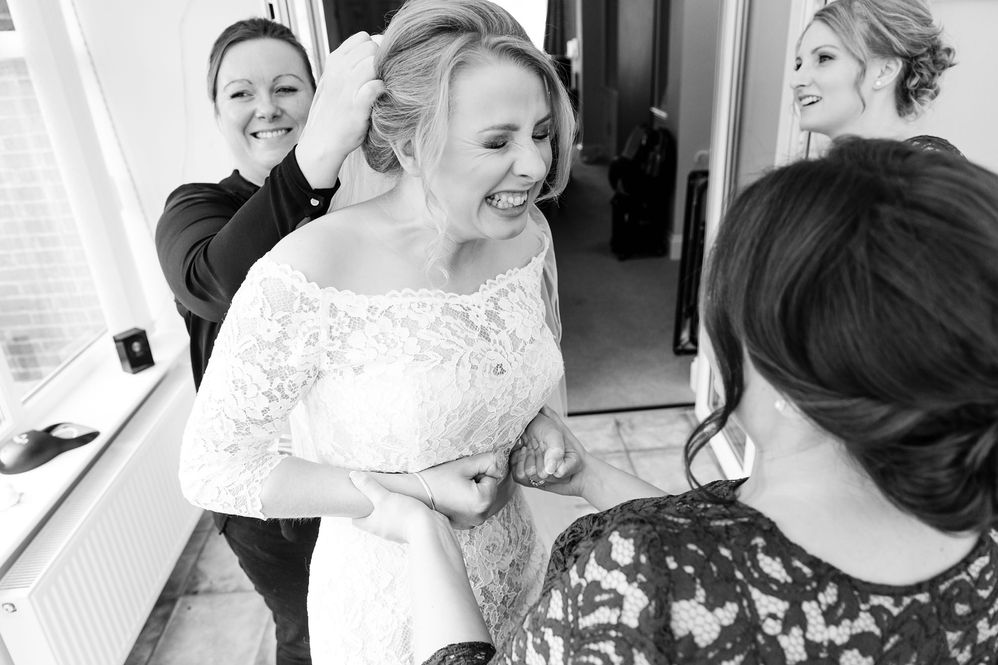 Bride makes silly face when putting in veil at York wedding