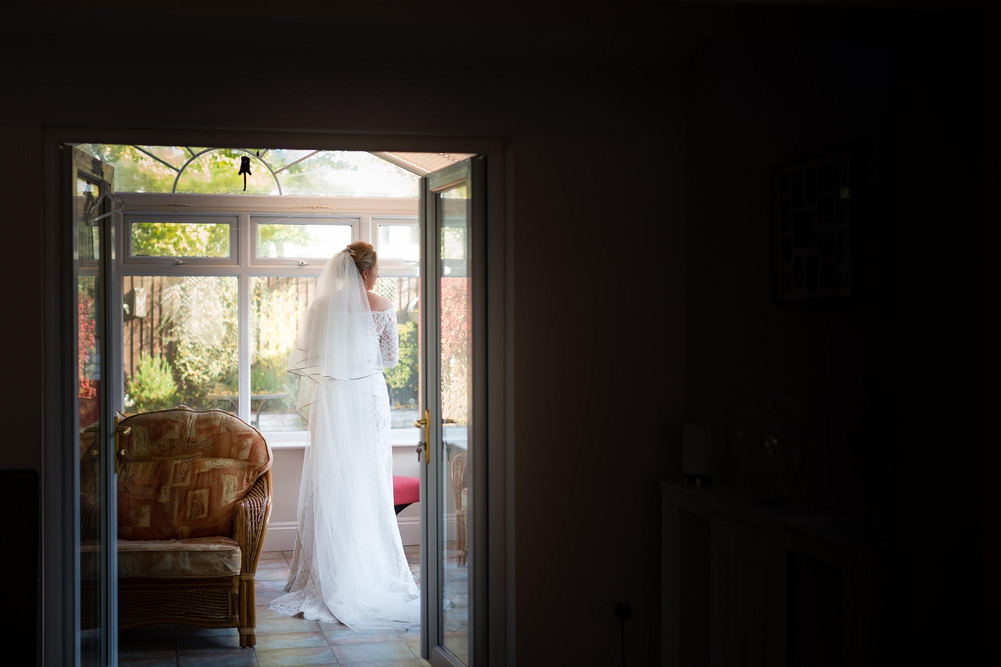 Full length photograph of bride framed in doorway