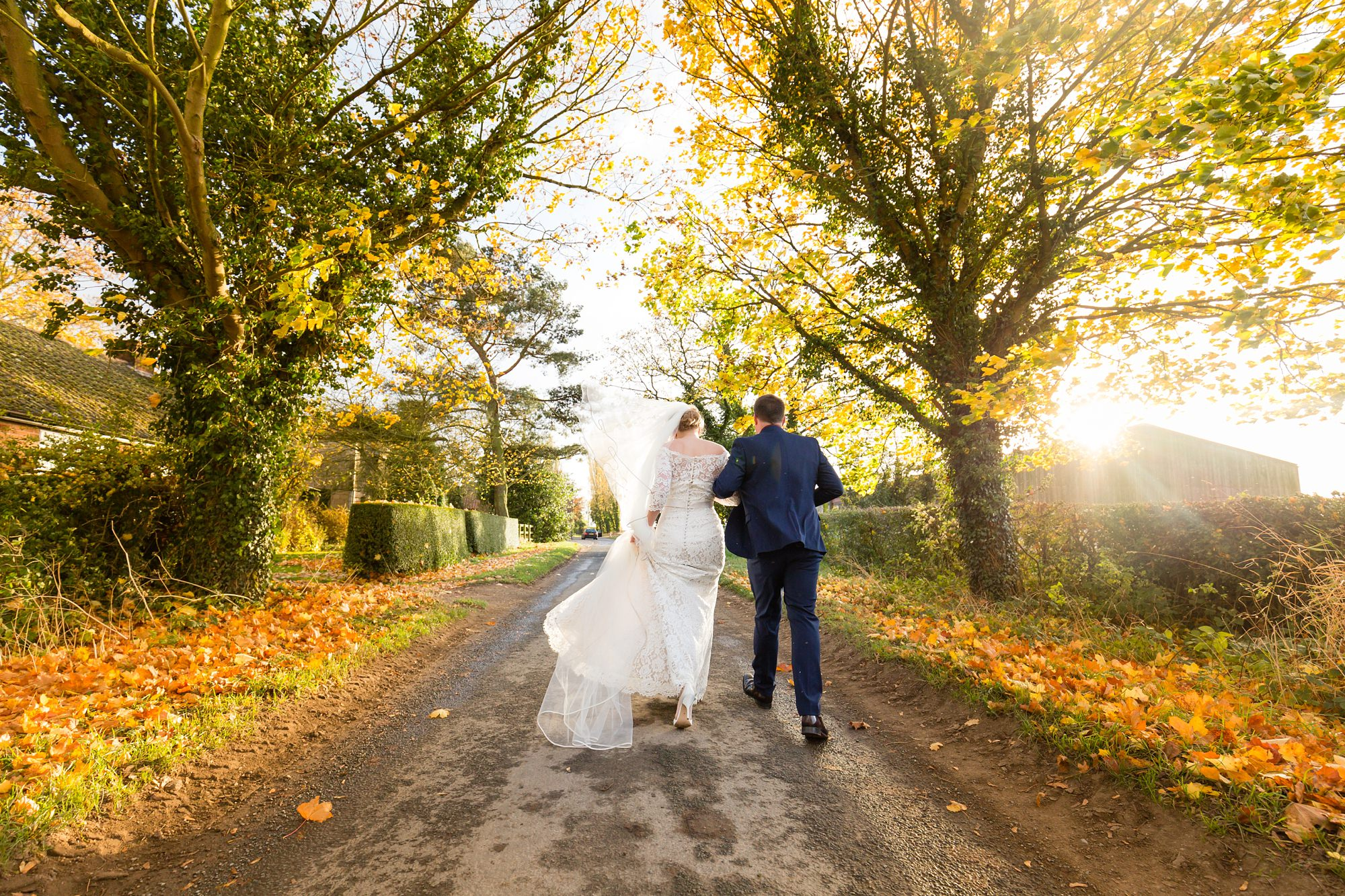 Bride and groom walking up the street in the autumn at The Normans