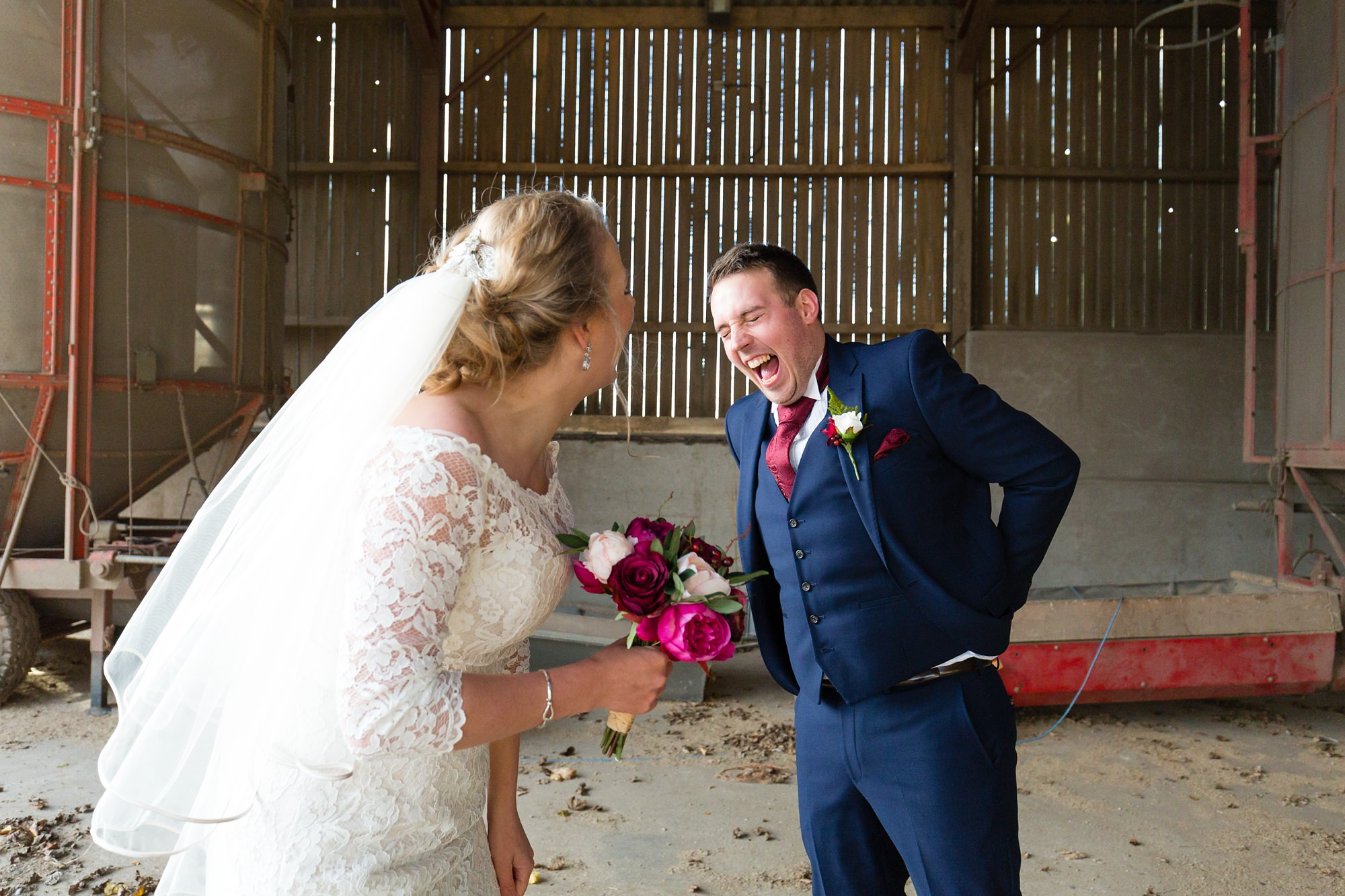 Bride & groom laughing in the barn at The Normans wedding venue in York
