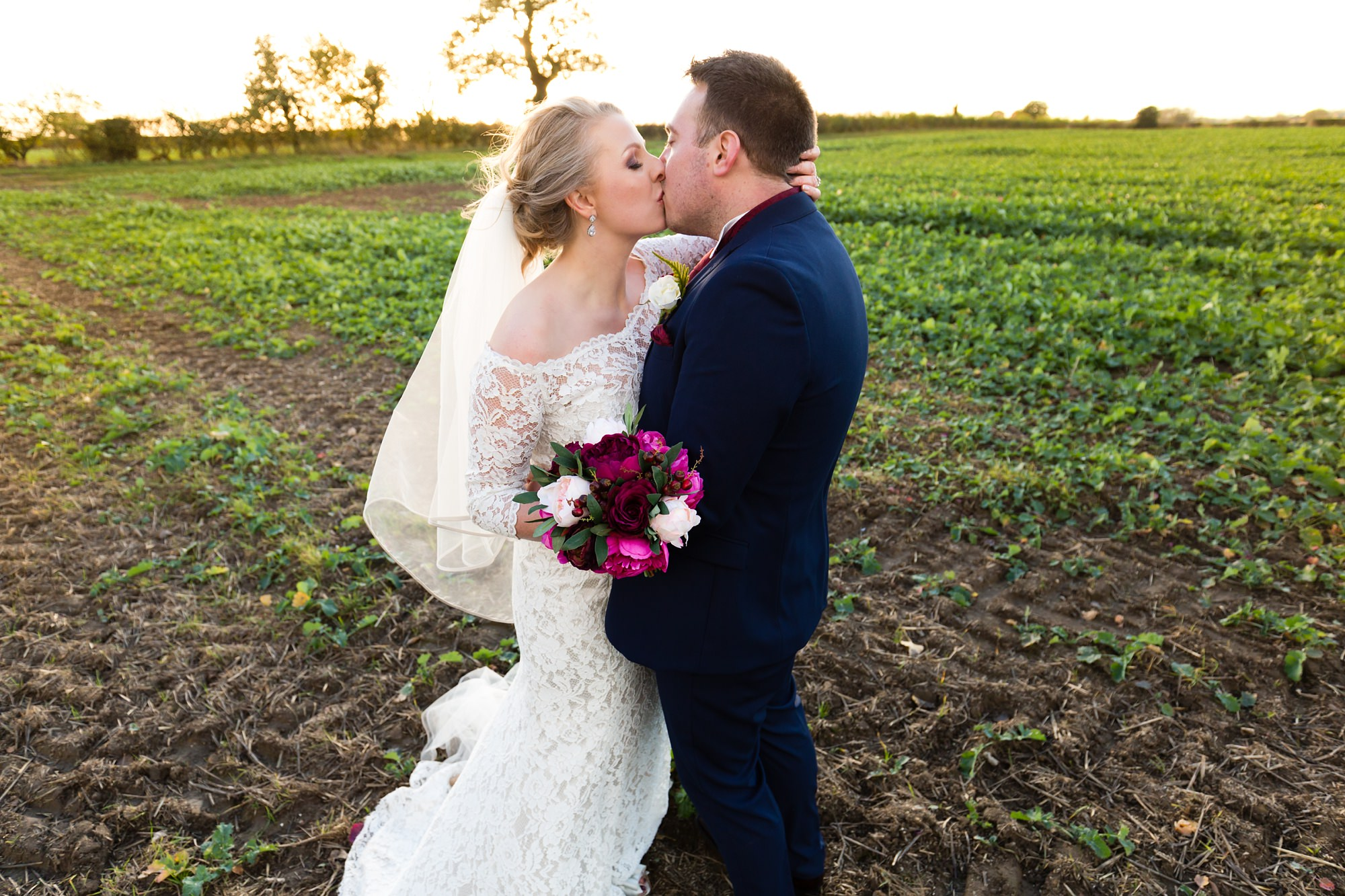 Bride & groom kiss in the fields at The Normans wedding venue in York