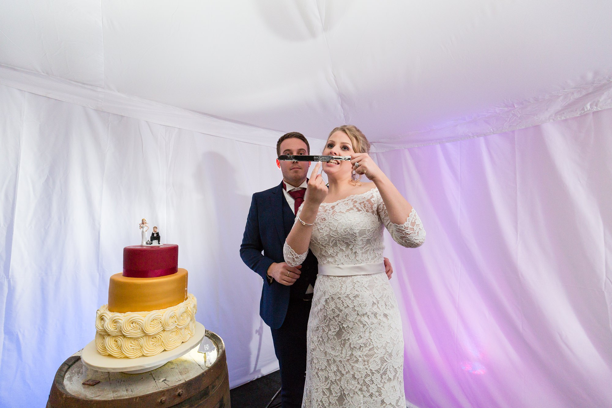 Funny bride shows off engraving on the cake knife at The Normans