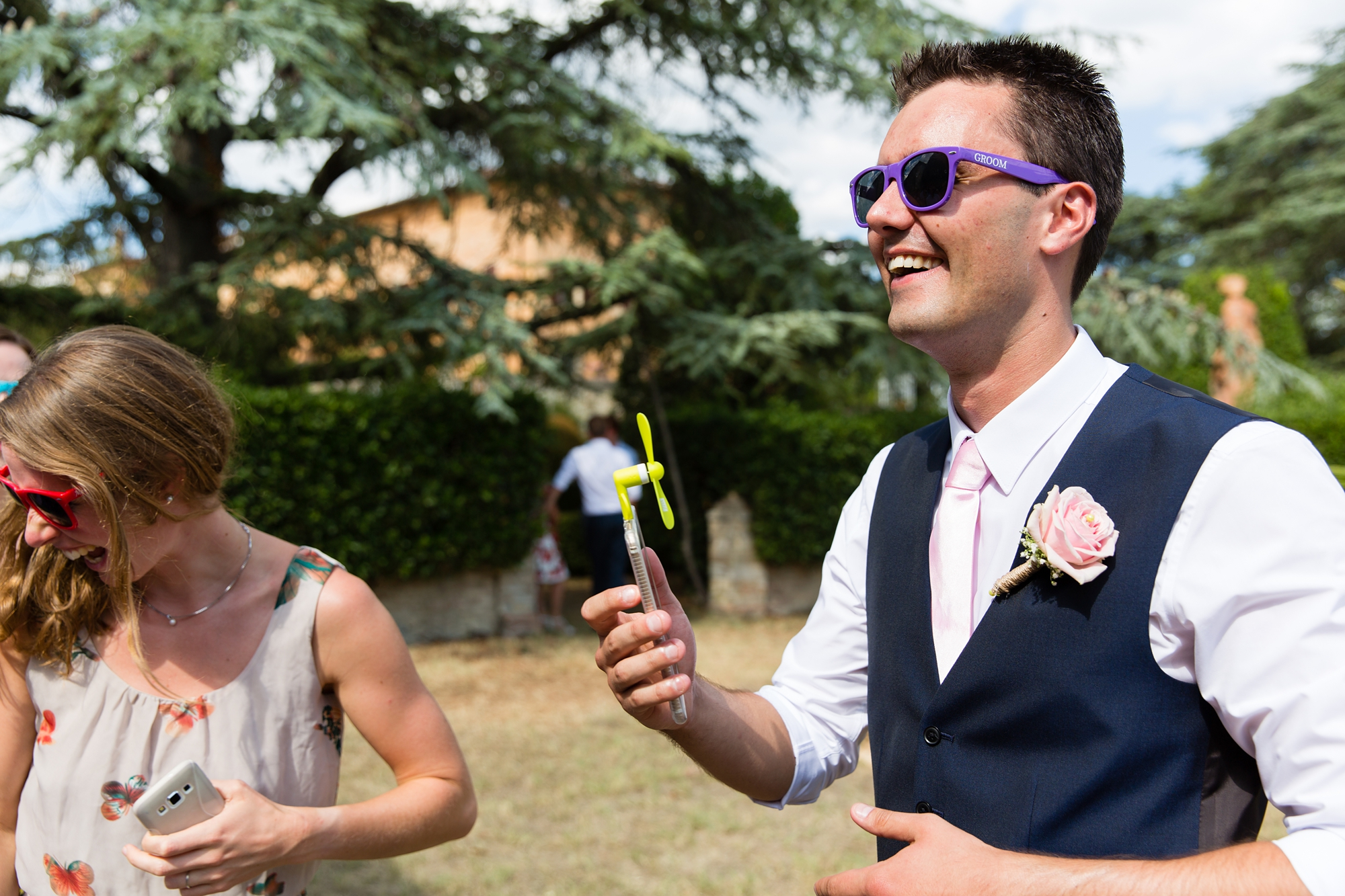 Villa Catignano Siena Wedding Photography groom in sunglasses with portable fan