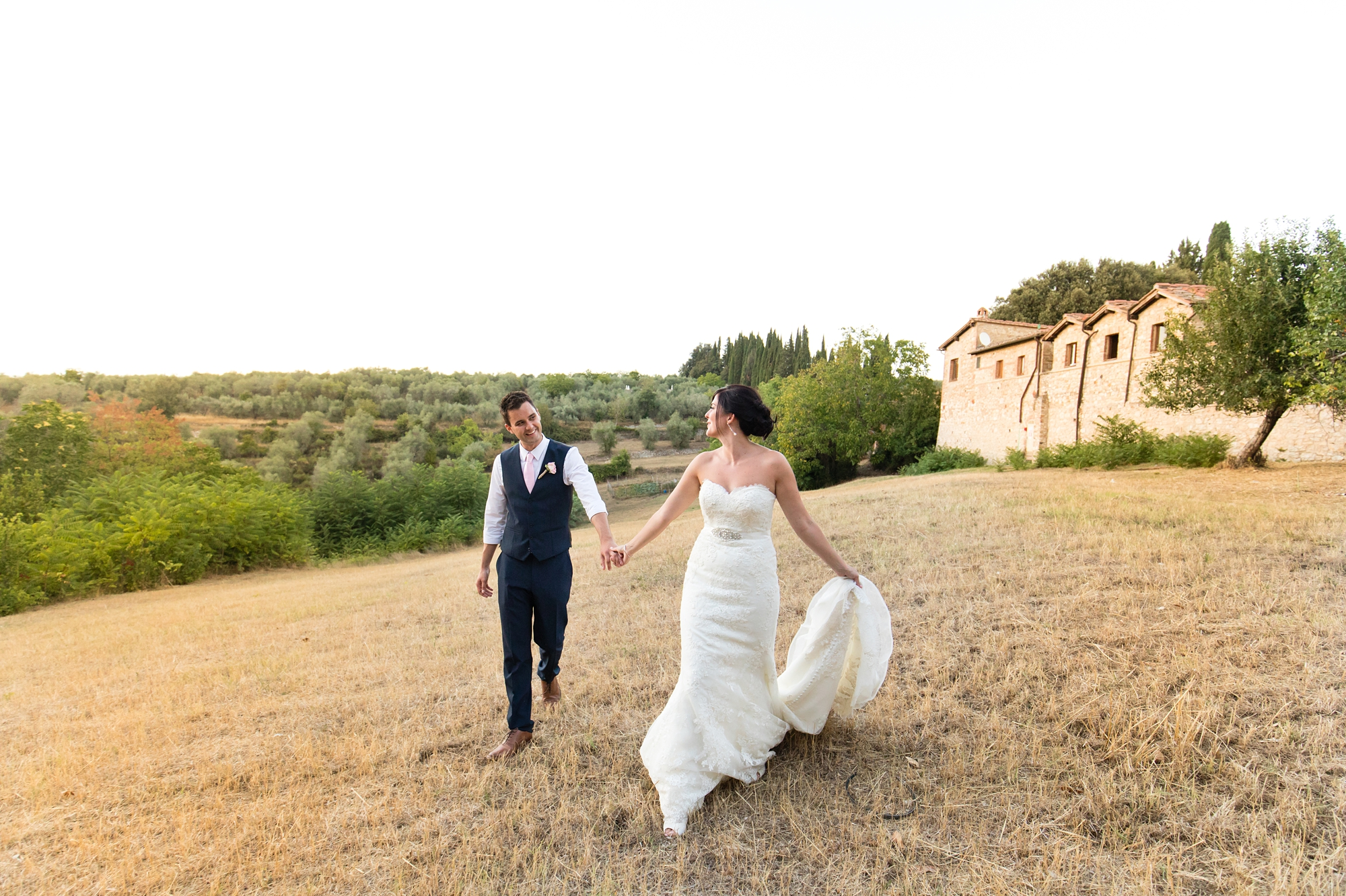 Villa Catignano Siena Wedding Photography bride and groom walk through fields in Italy