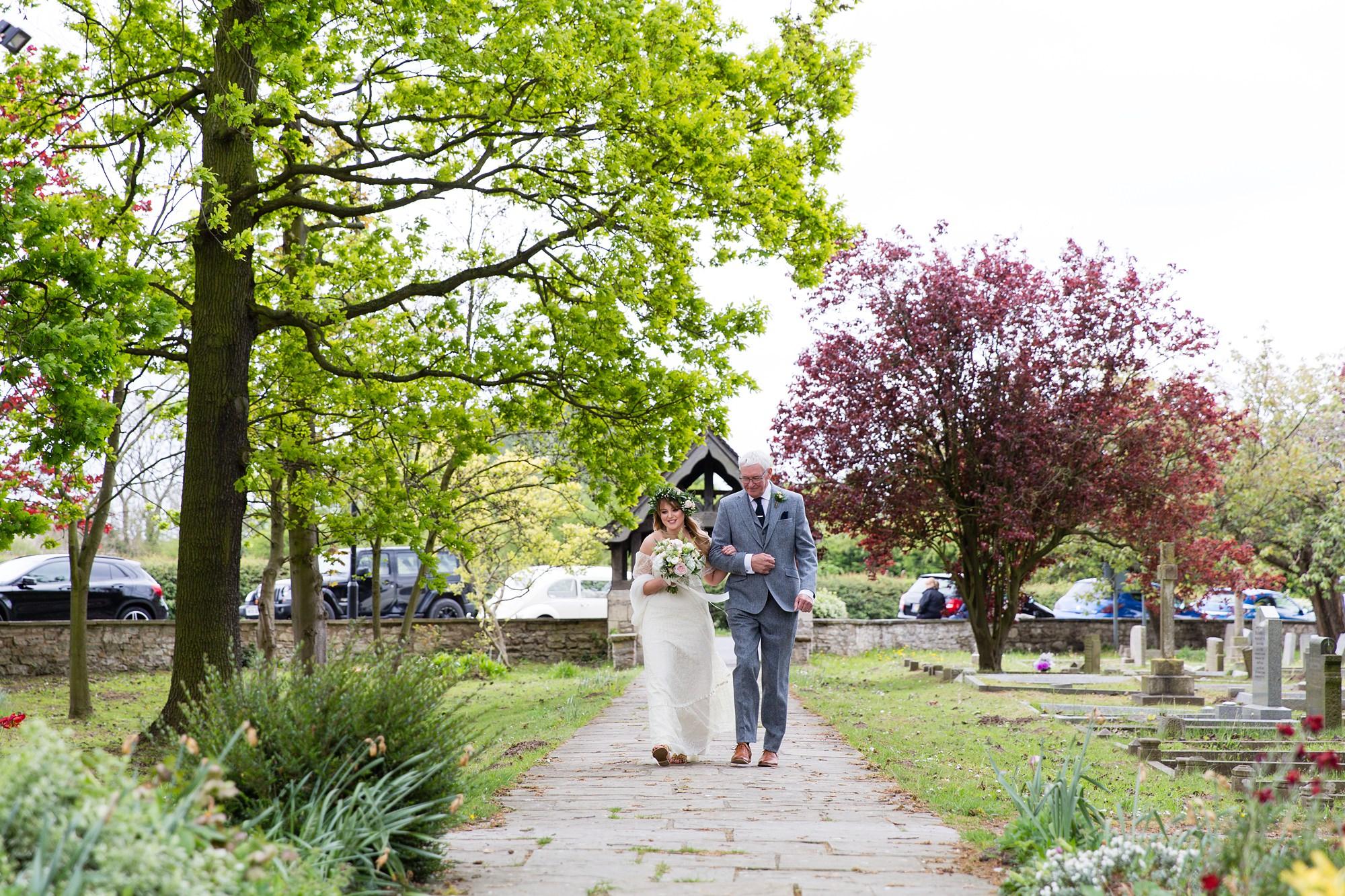 Villa farm wedding photography bride walks up to church with dad