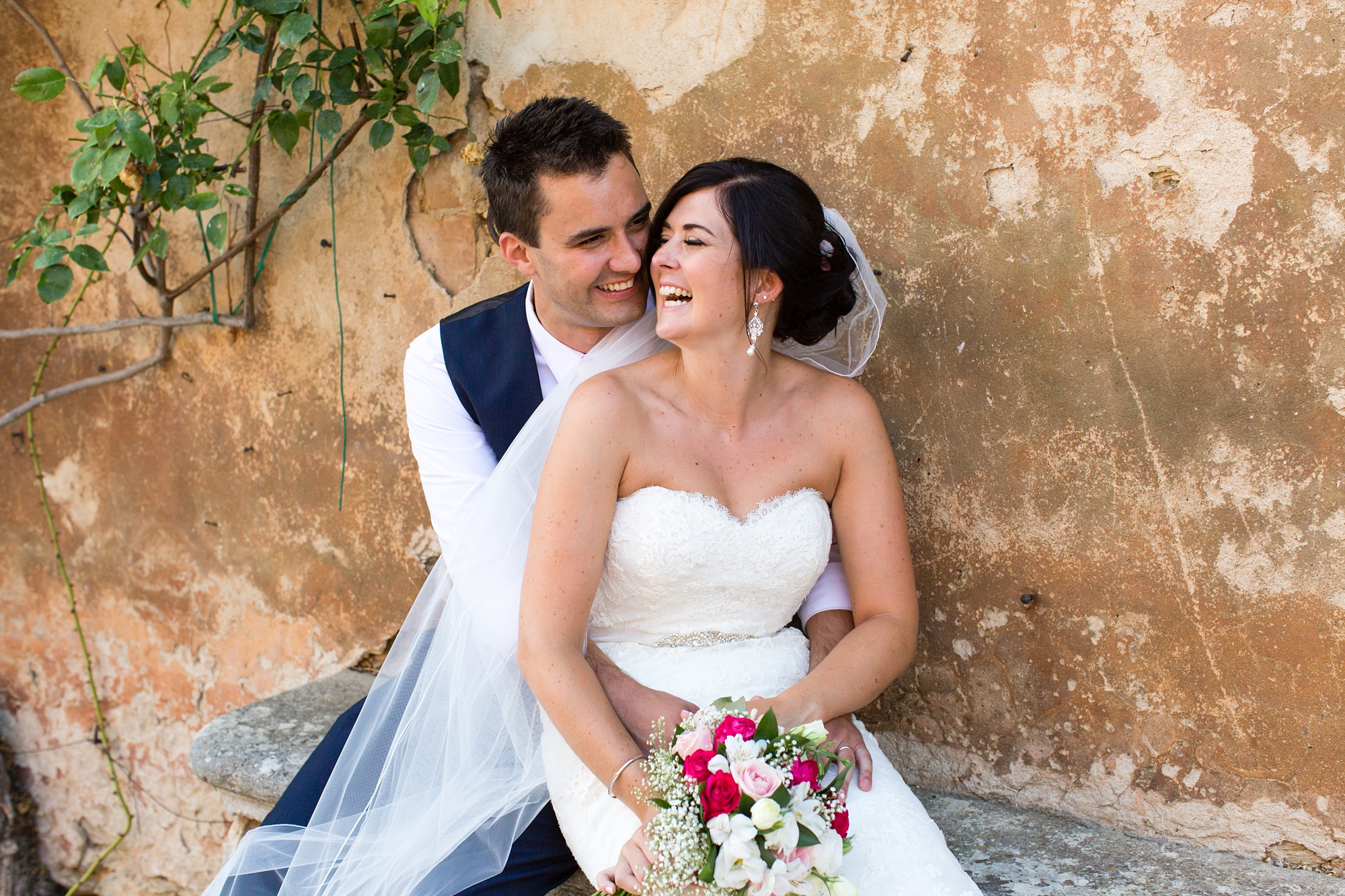 Couple laugh in front of Tuscan wall