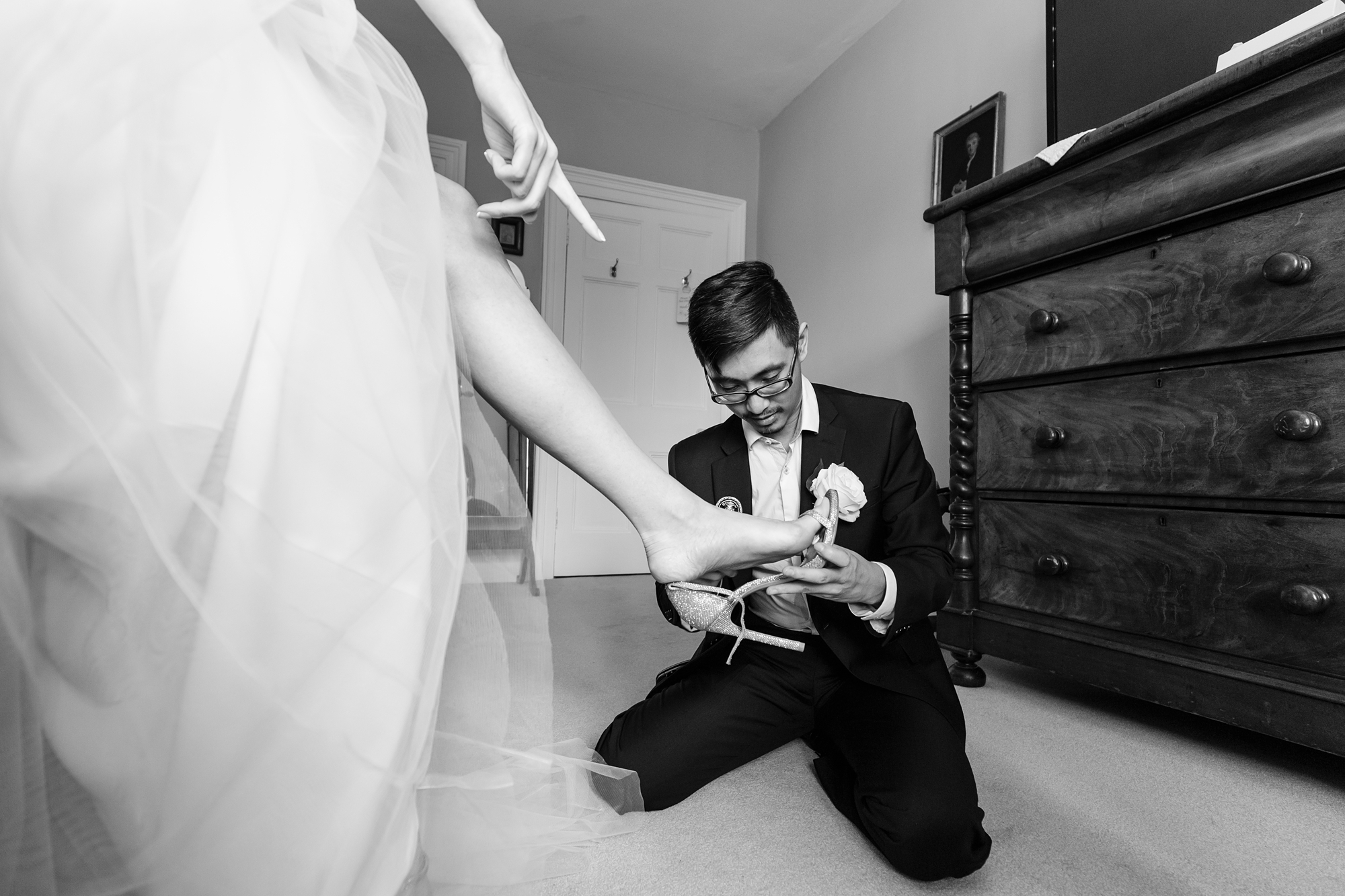 Bride points to shoe whilst groomsman buckles it funny wedding photos york