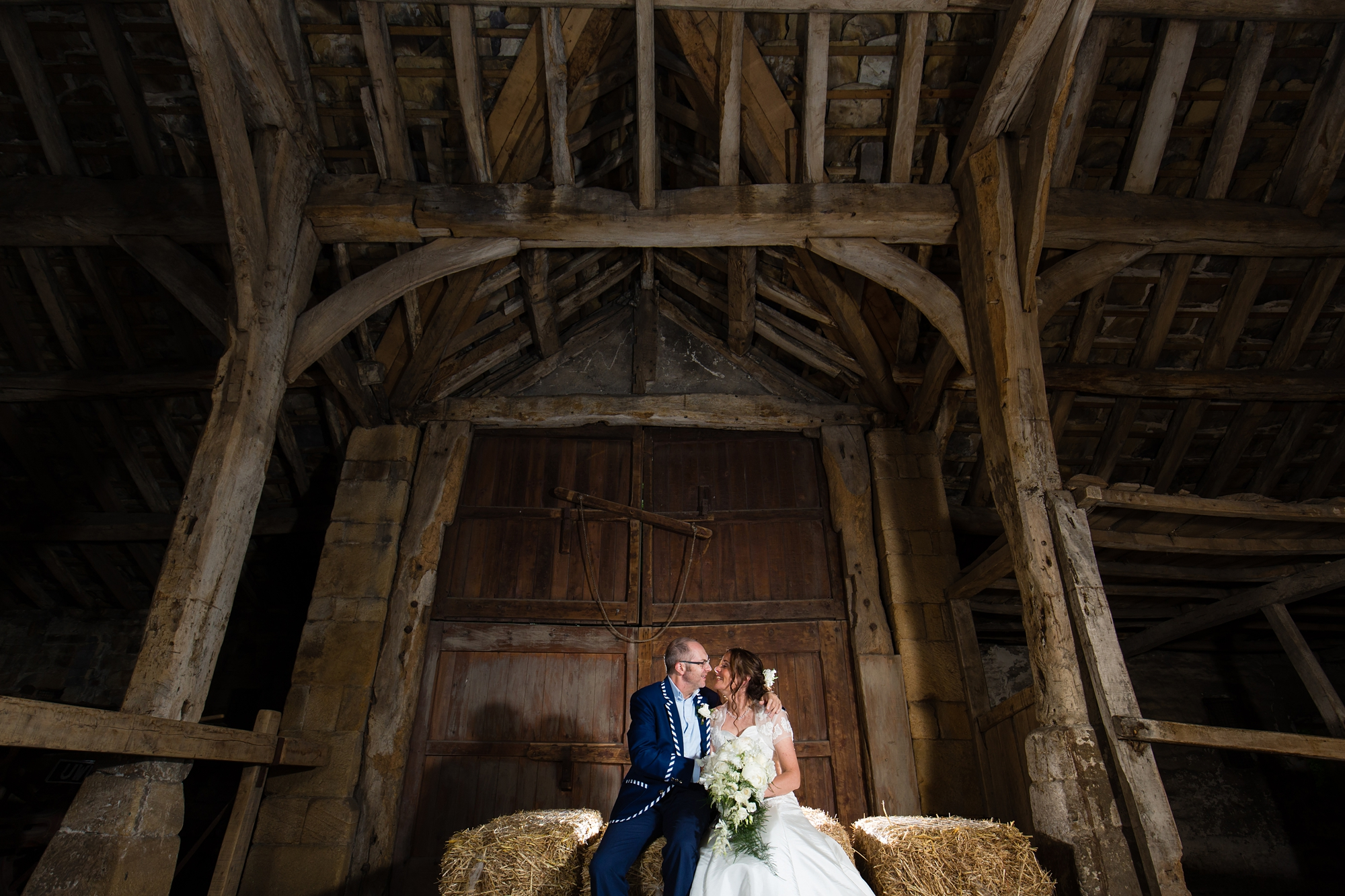 Bride and groom on haybeale in barn at East Riddlesden Hall