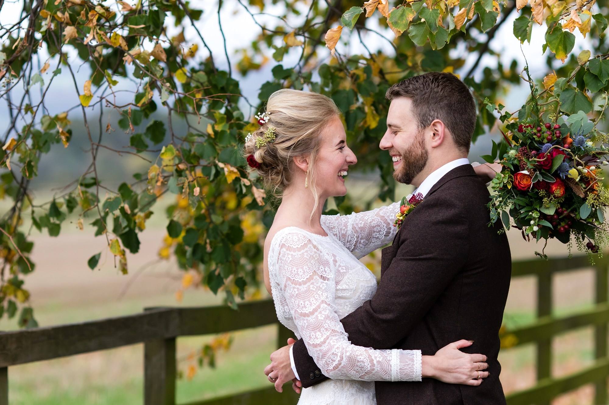 Bride and groom kiss and cuddle under autumn tree at york wedding
