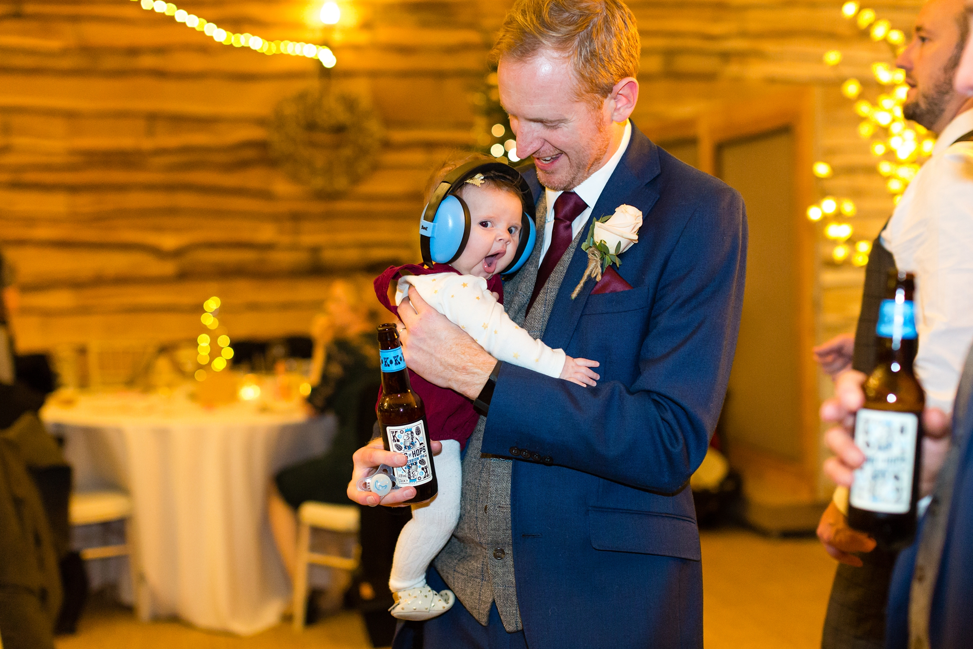 Baby with ear protection at wedding party in york