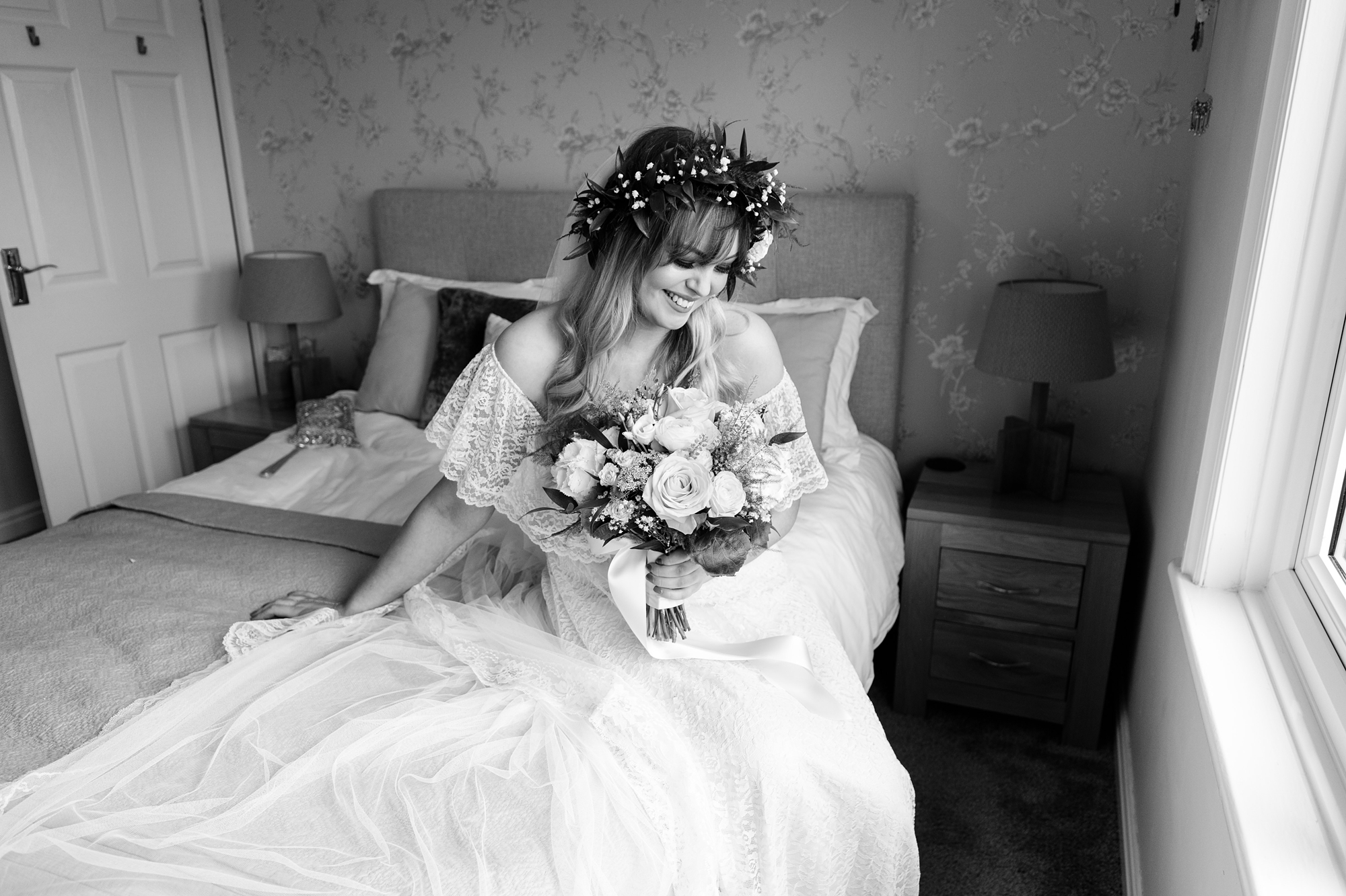 Tux and tales photography York bride sitting on bed with flowers