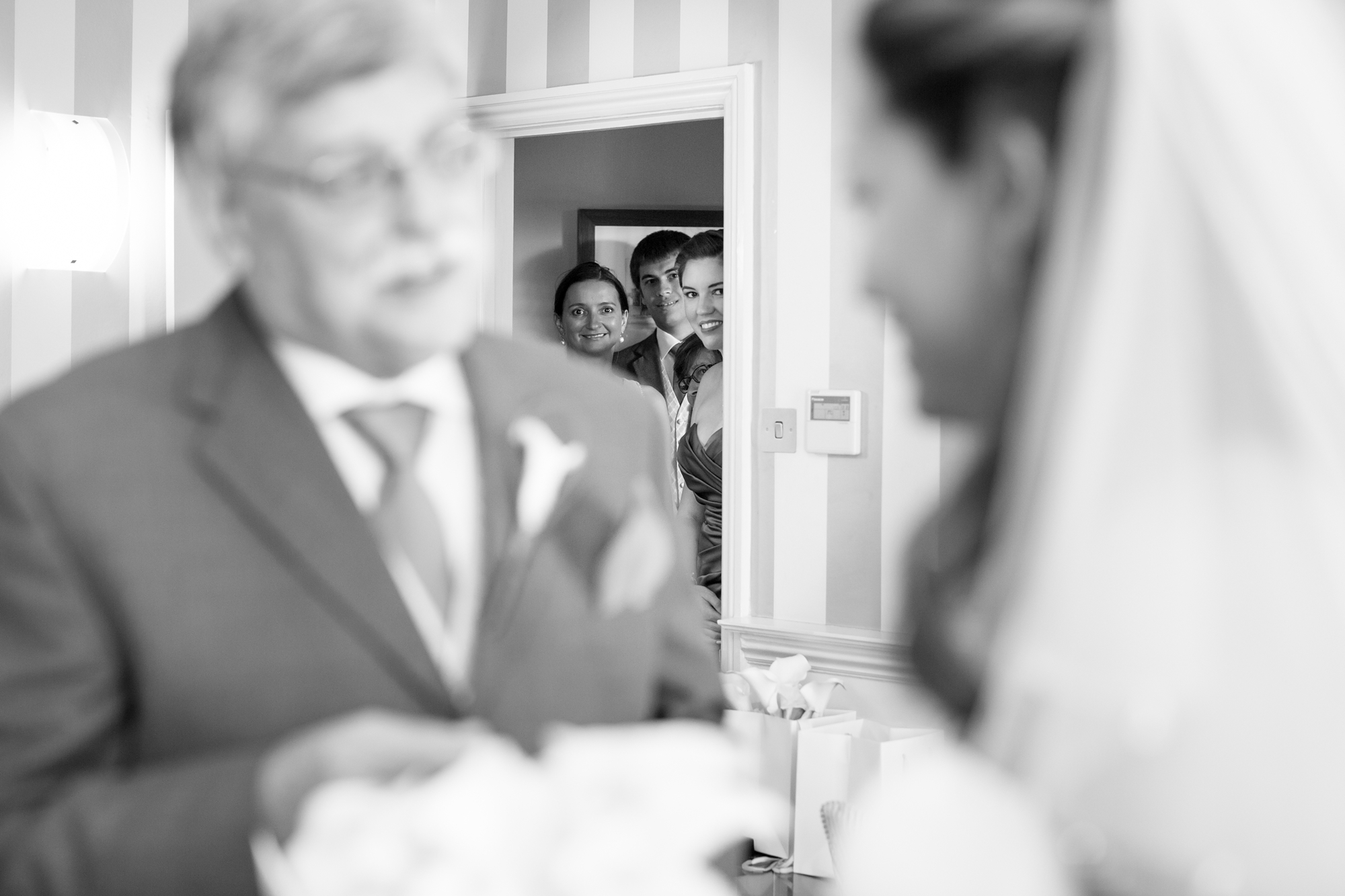 Looking on as dad sees bride at york wedding