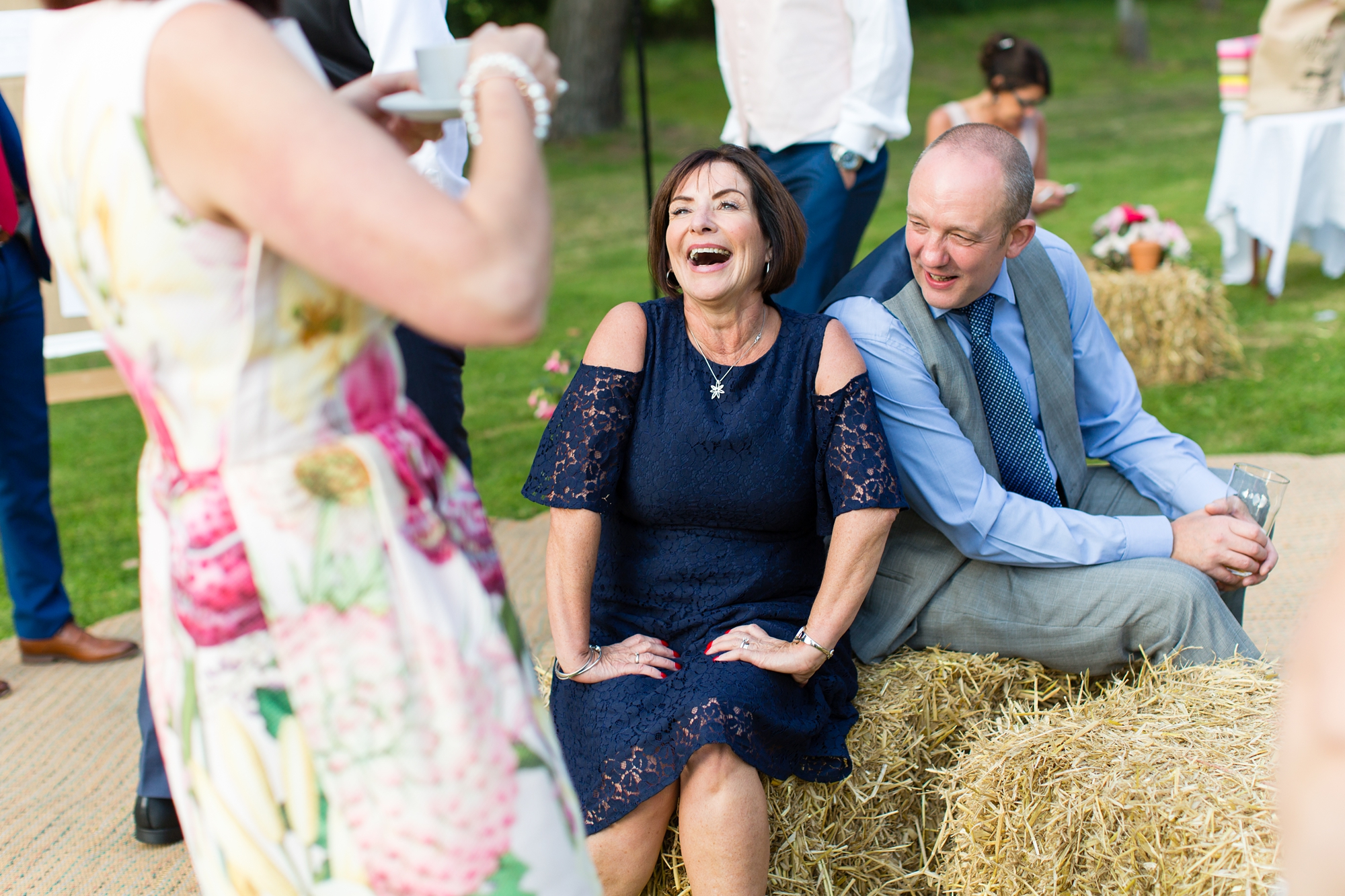 Guest laughing at york wedding sitting on haybale