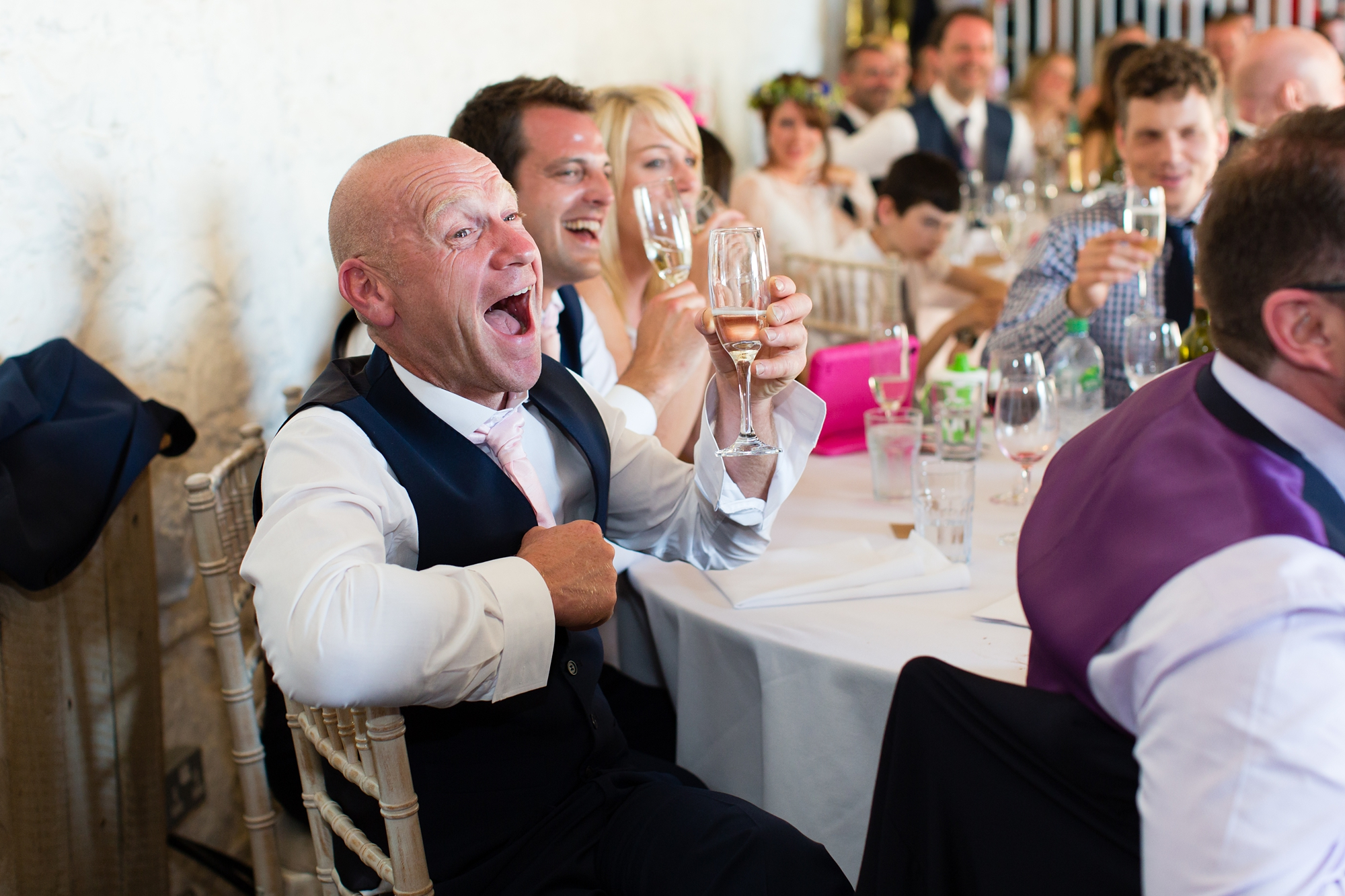 Guests laugh during speeches at wedding