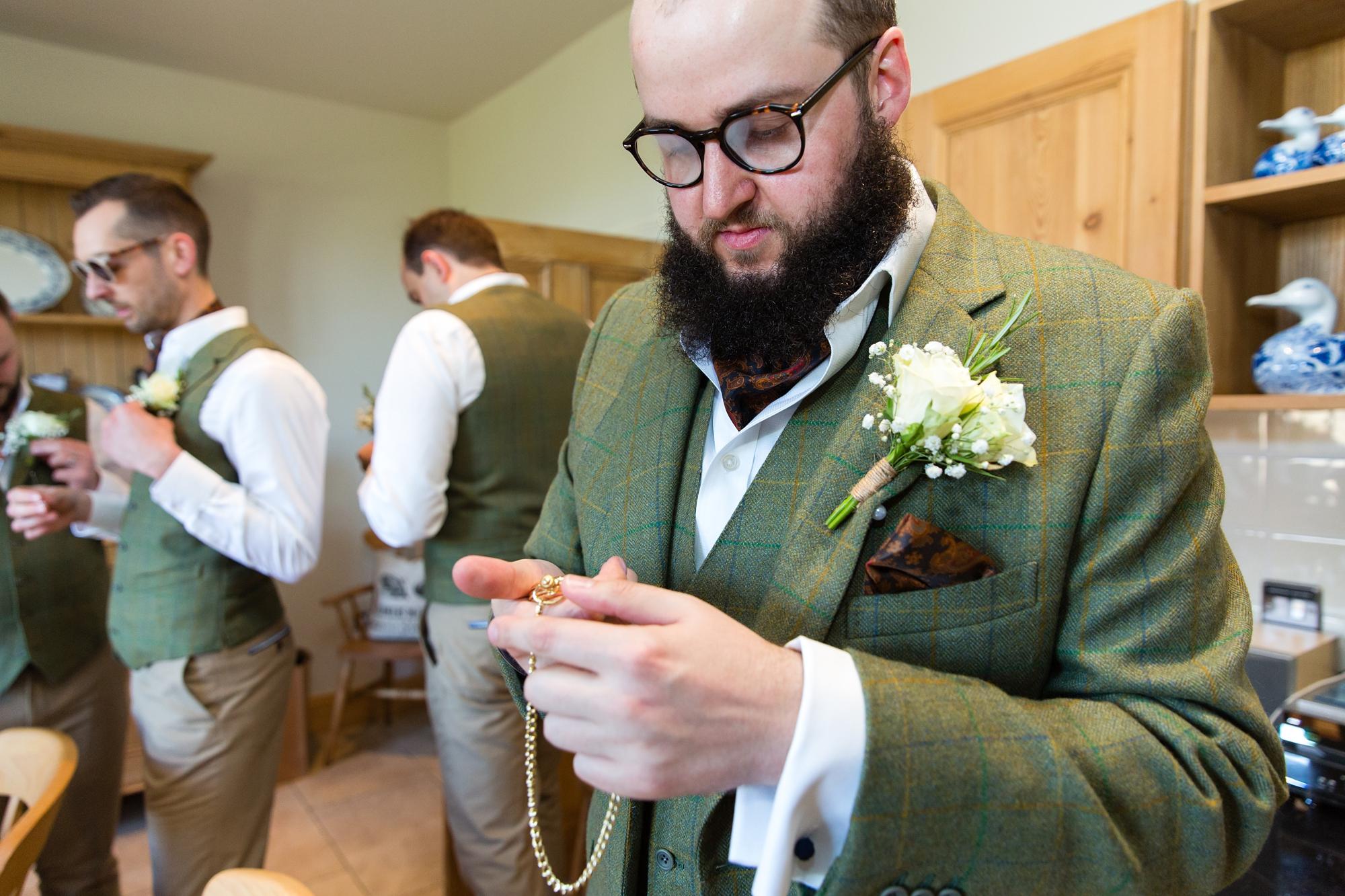 York Wedding Photography at Barmbyfield Barns groom looking at pocket watch gift