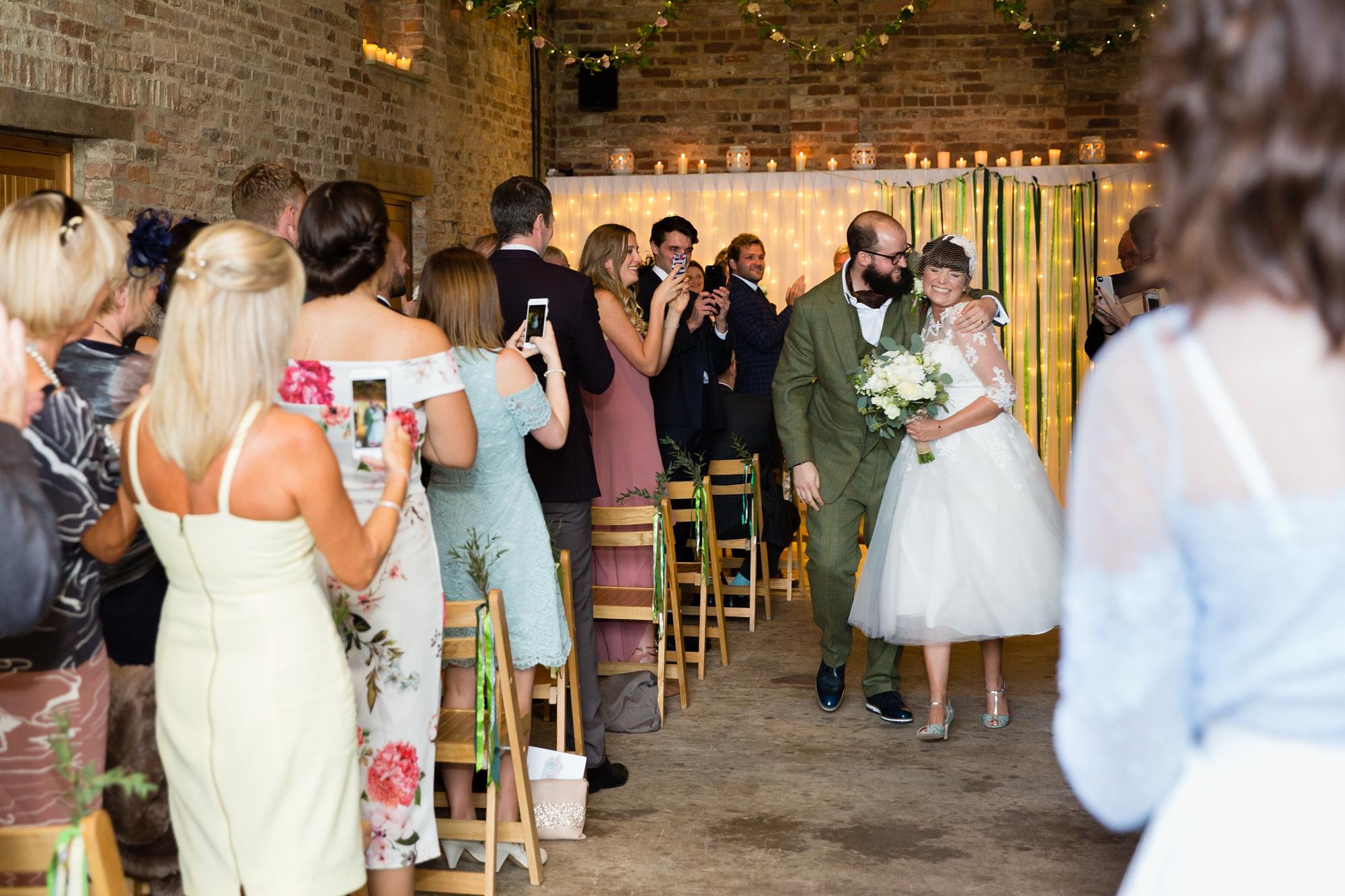 York Wedding Photography at Barmbyfield Barns walking back up the aisle