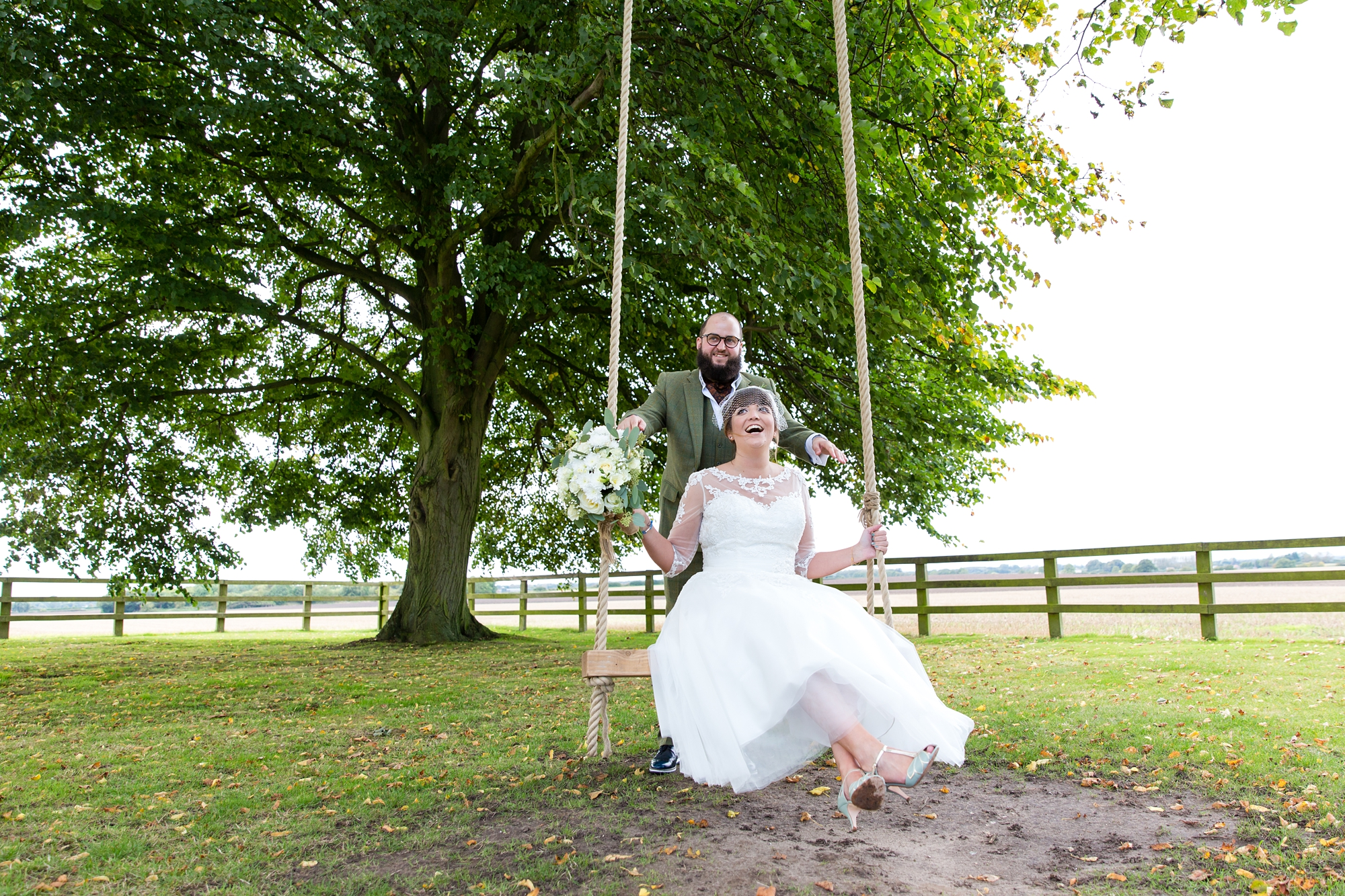 York Wedding Photography at Barmbyfield Barns groom pushes bride on swing