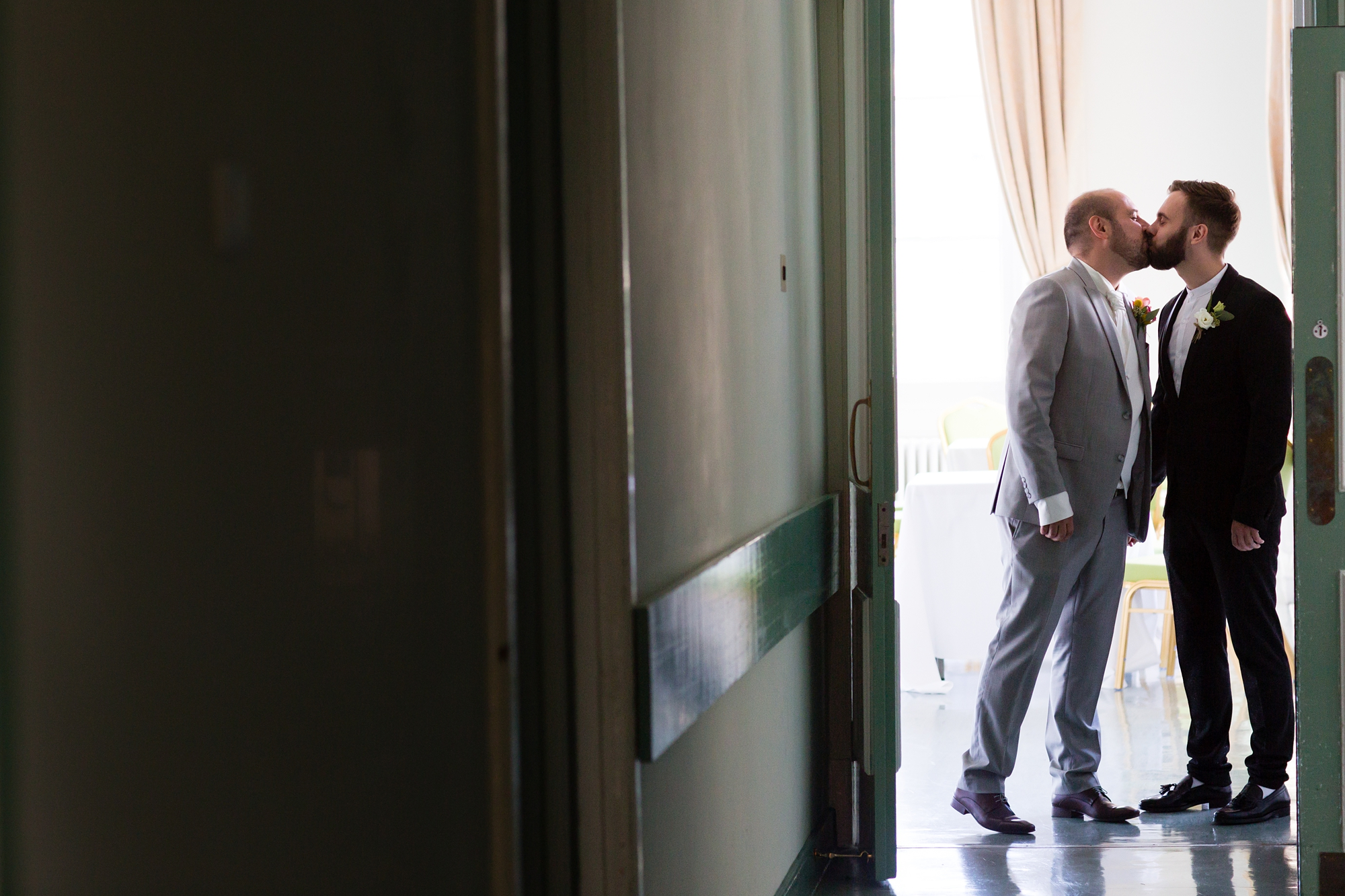 Grooms kissing before ceremony at same sex wedding