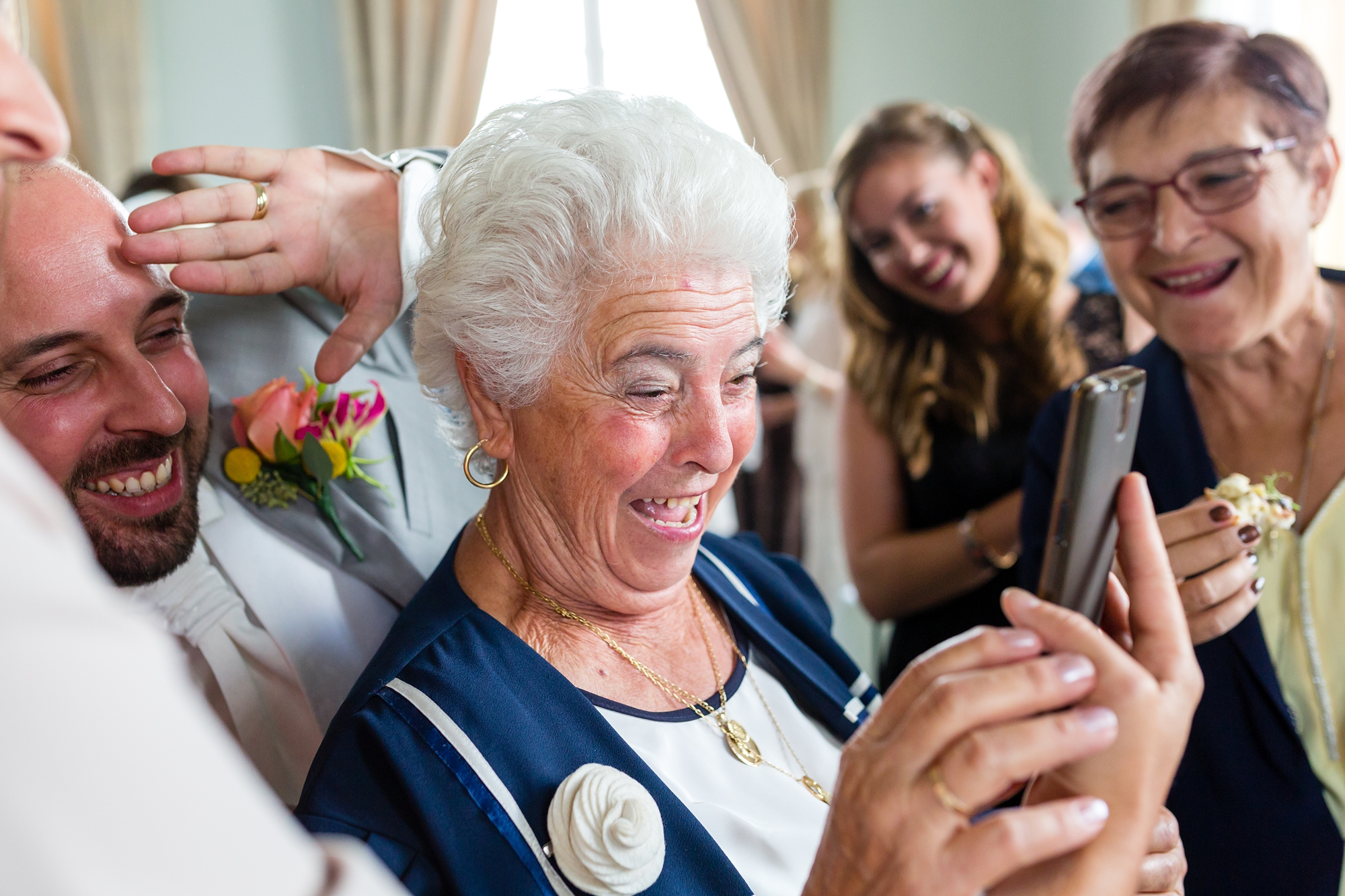A fun Yorkshire Wedding grooms mother smiles and laughs on skype call with family