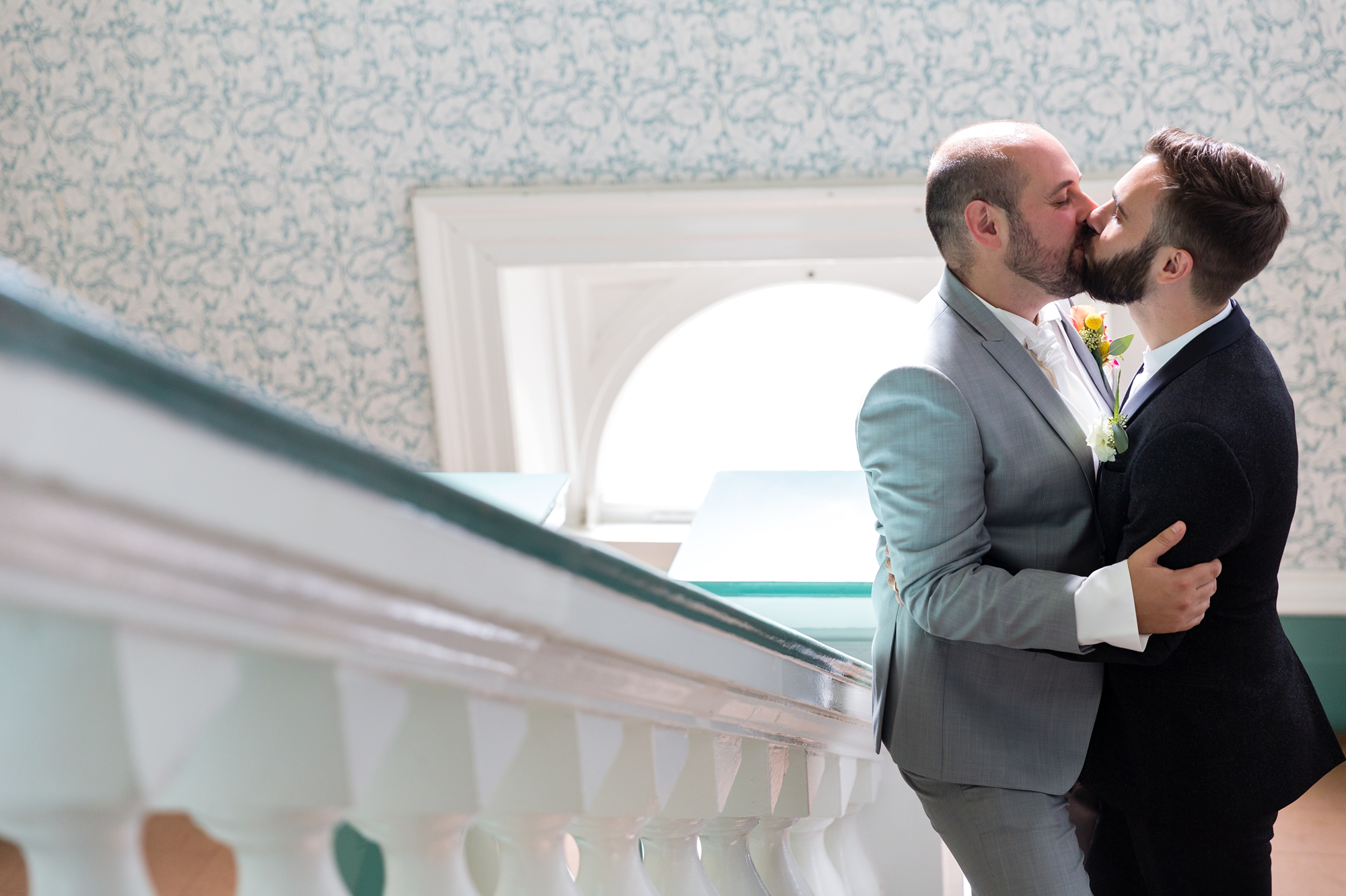 A fun Yorkshire Wedding grooms kissing in front of beautiful patterned wallpaper