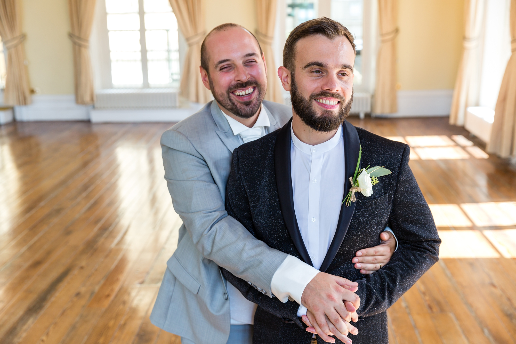 A fun Yorkshire Wedding grooms cuddling in ballroom
