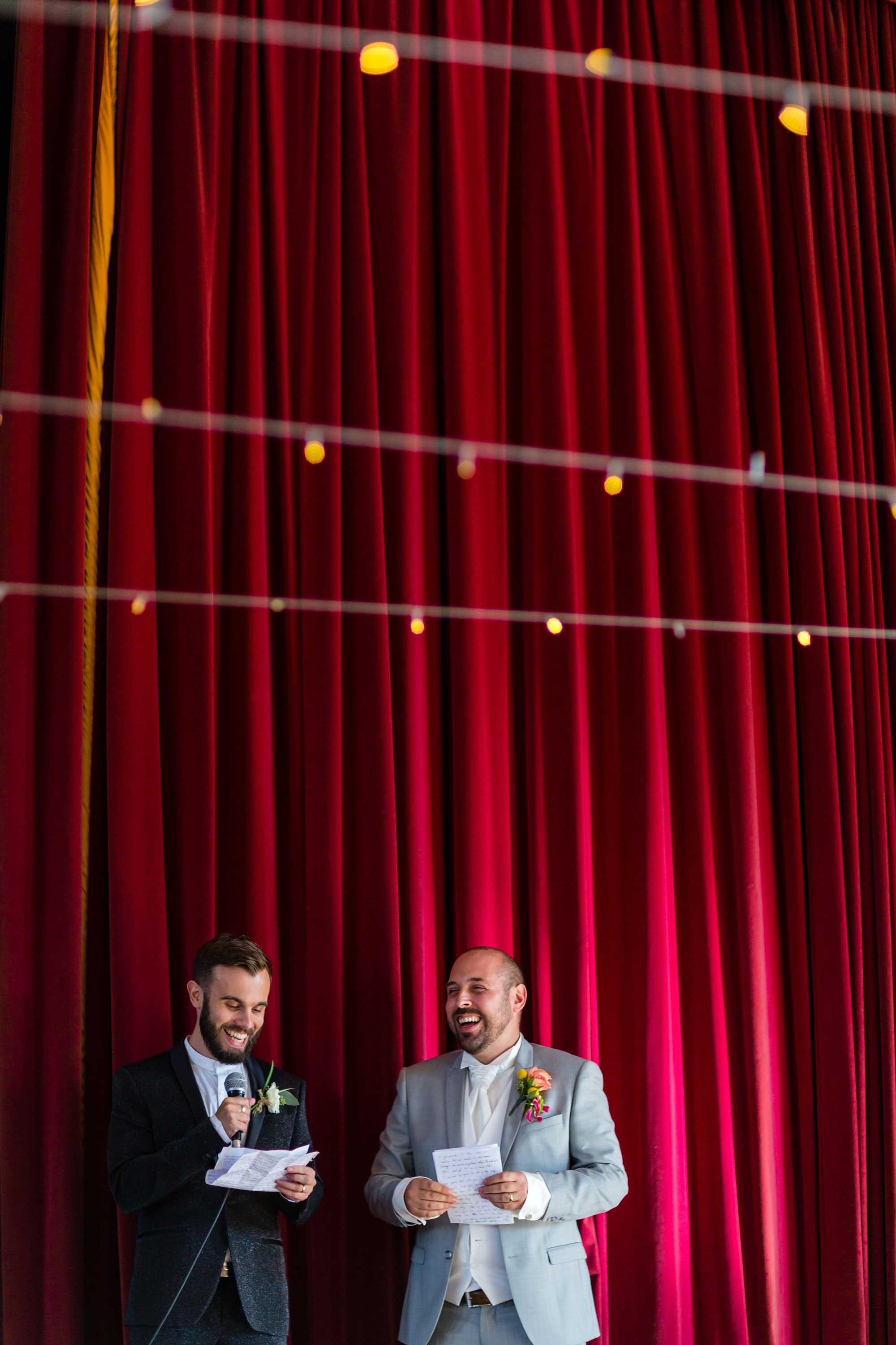 Grooms giving speeches in front of red curtain