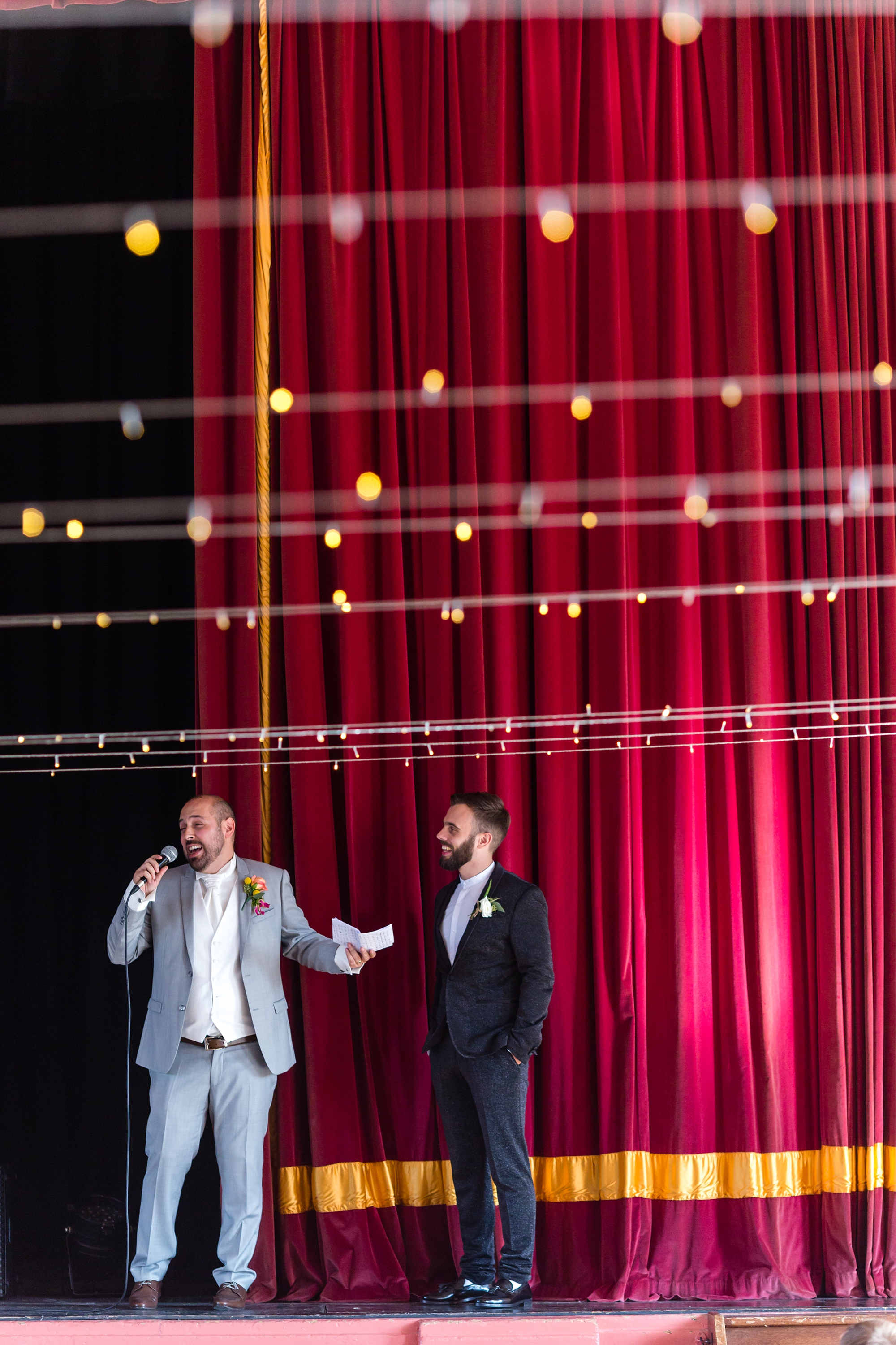 Grooms giving speeches in front of red curtain A fun Yorkshire Wedding