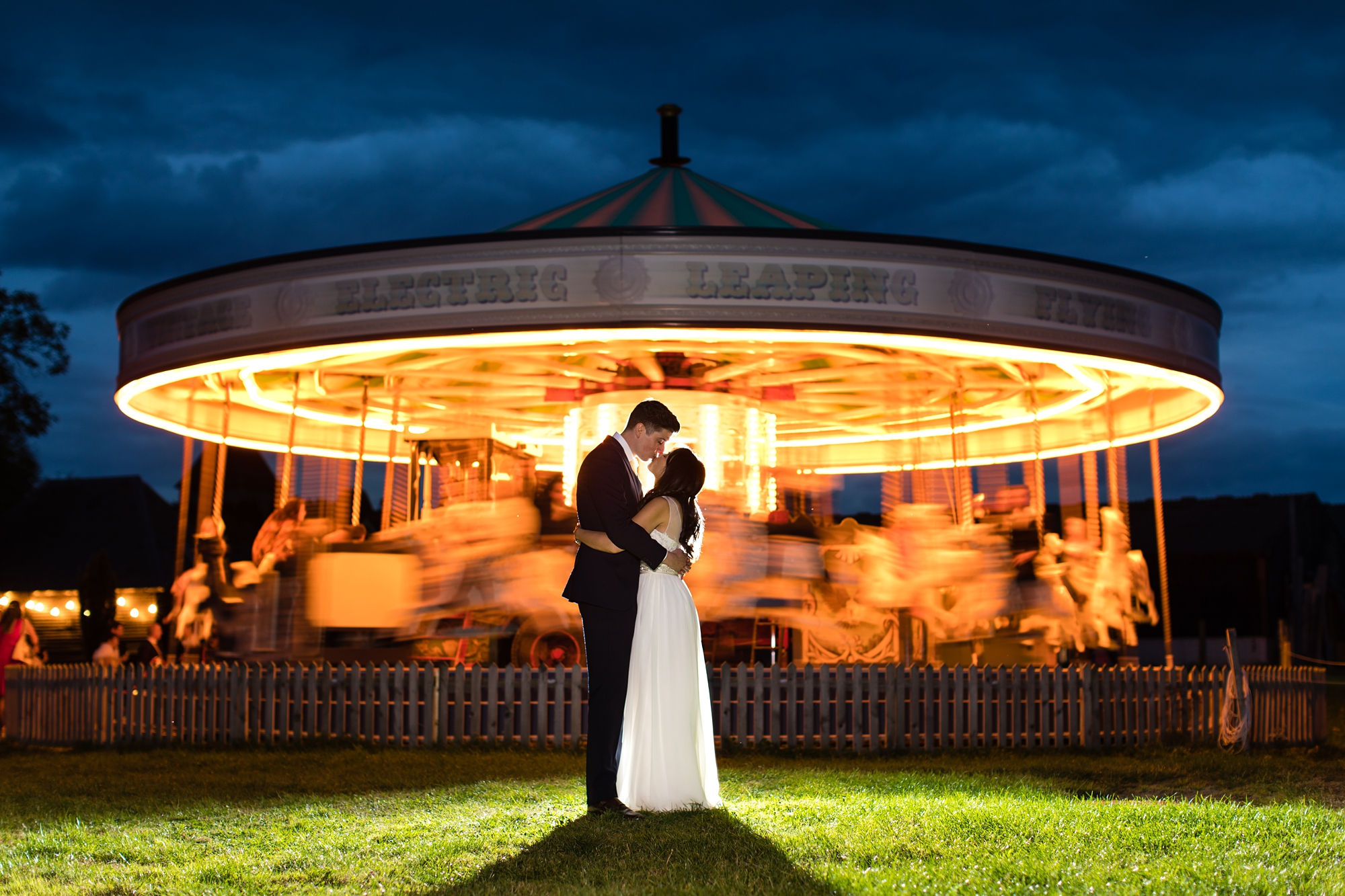 Preston Court Wedding Photography hero shot of couple in front of carousel with stormy skies