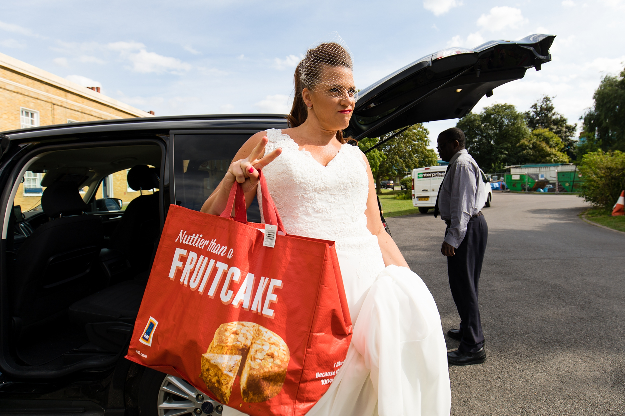 Bride giving peace symbol and holding Aldi bag at London wedding
