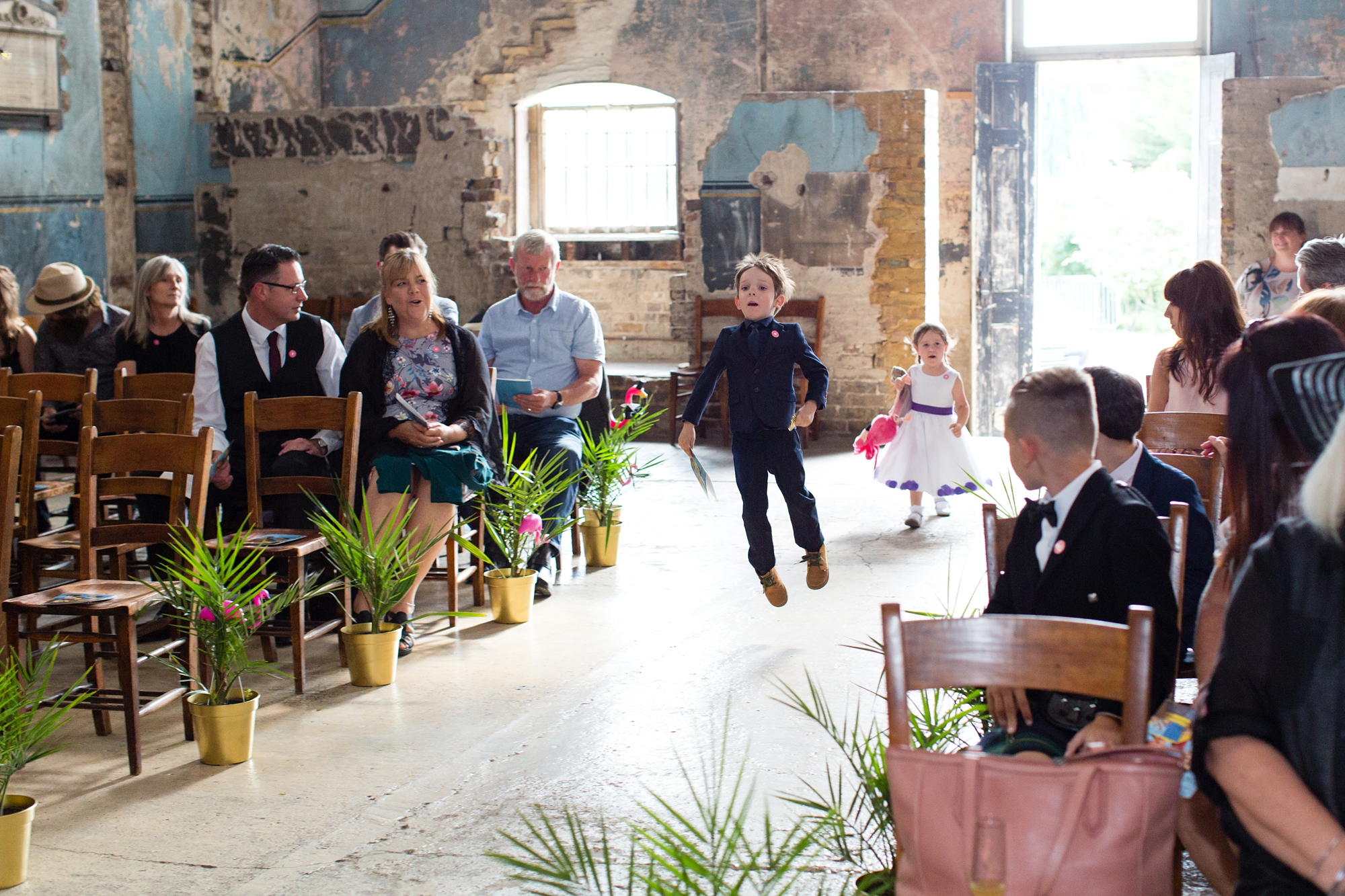 Ring bearer skips up the aisle at wedding at Asylum chapel in London