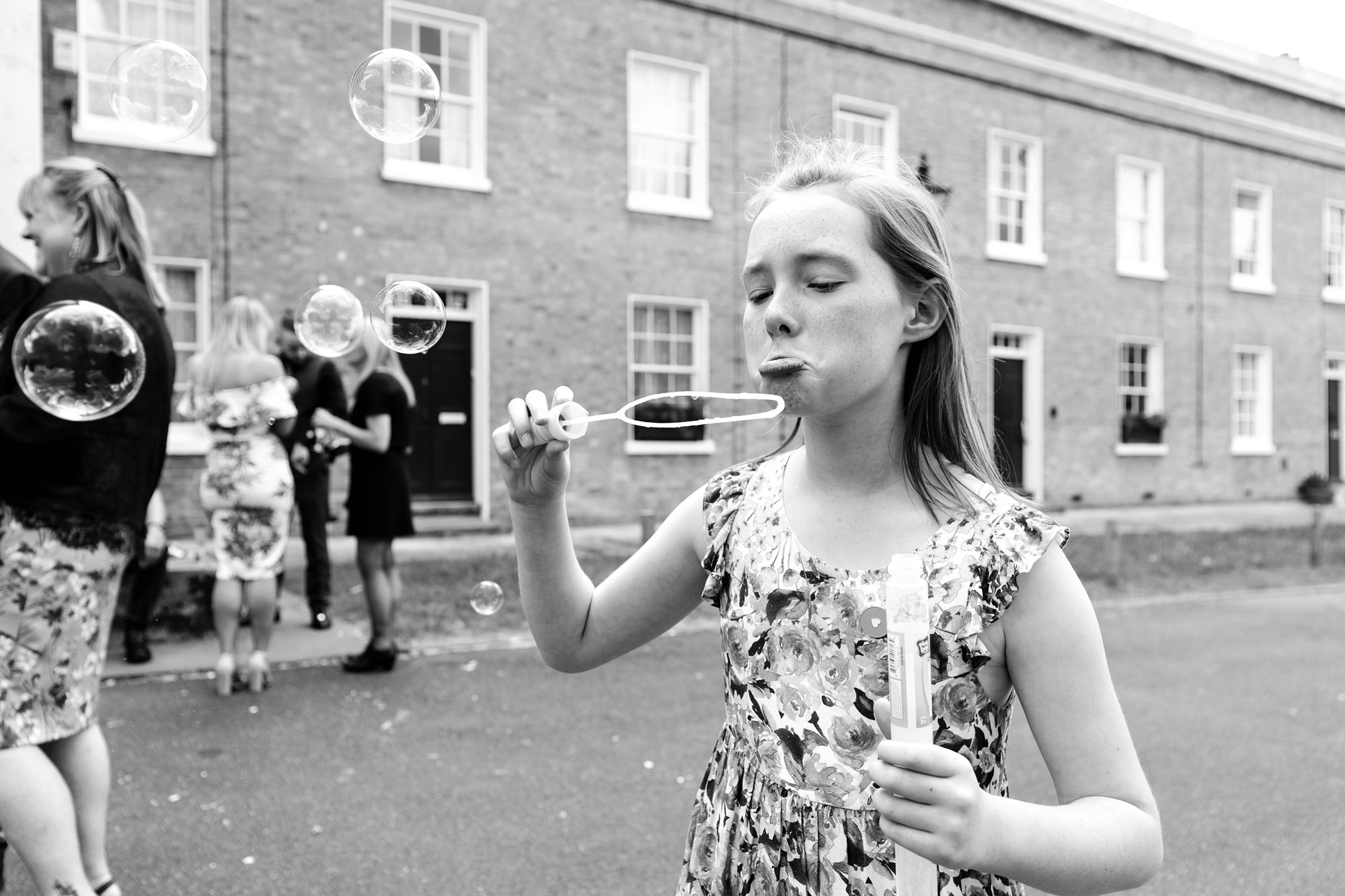 Little girl pouts in front of bubbles at quirky wedding in London