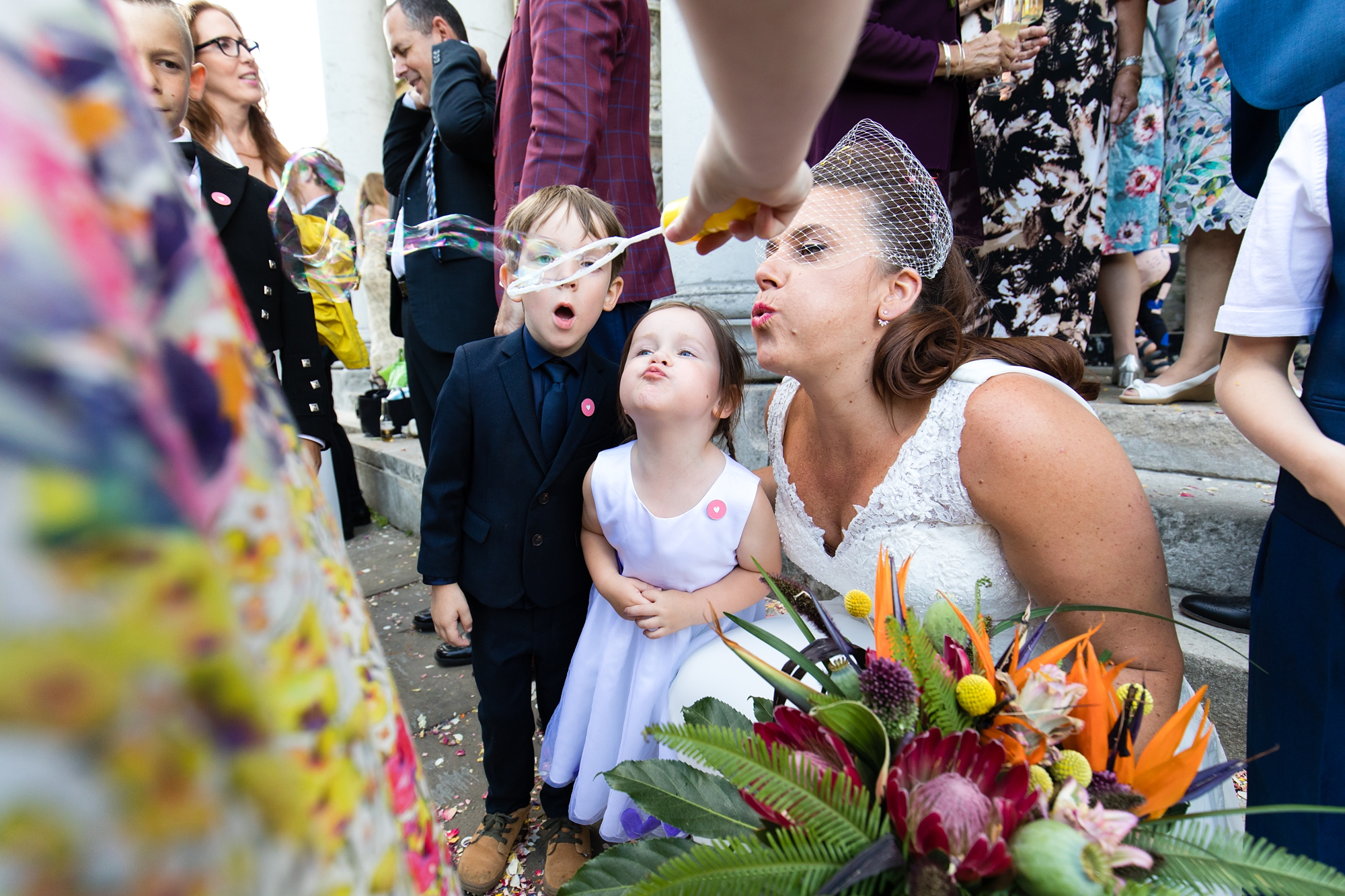 Bride blows bubbles with kids at wedding at the Asylum in London