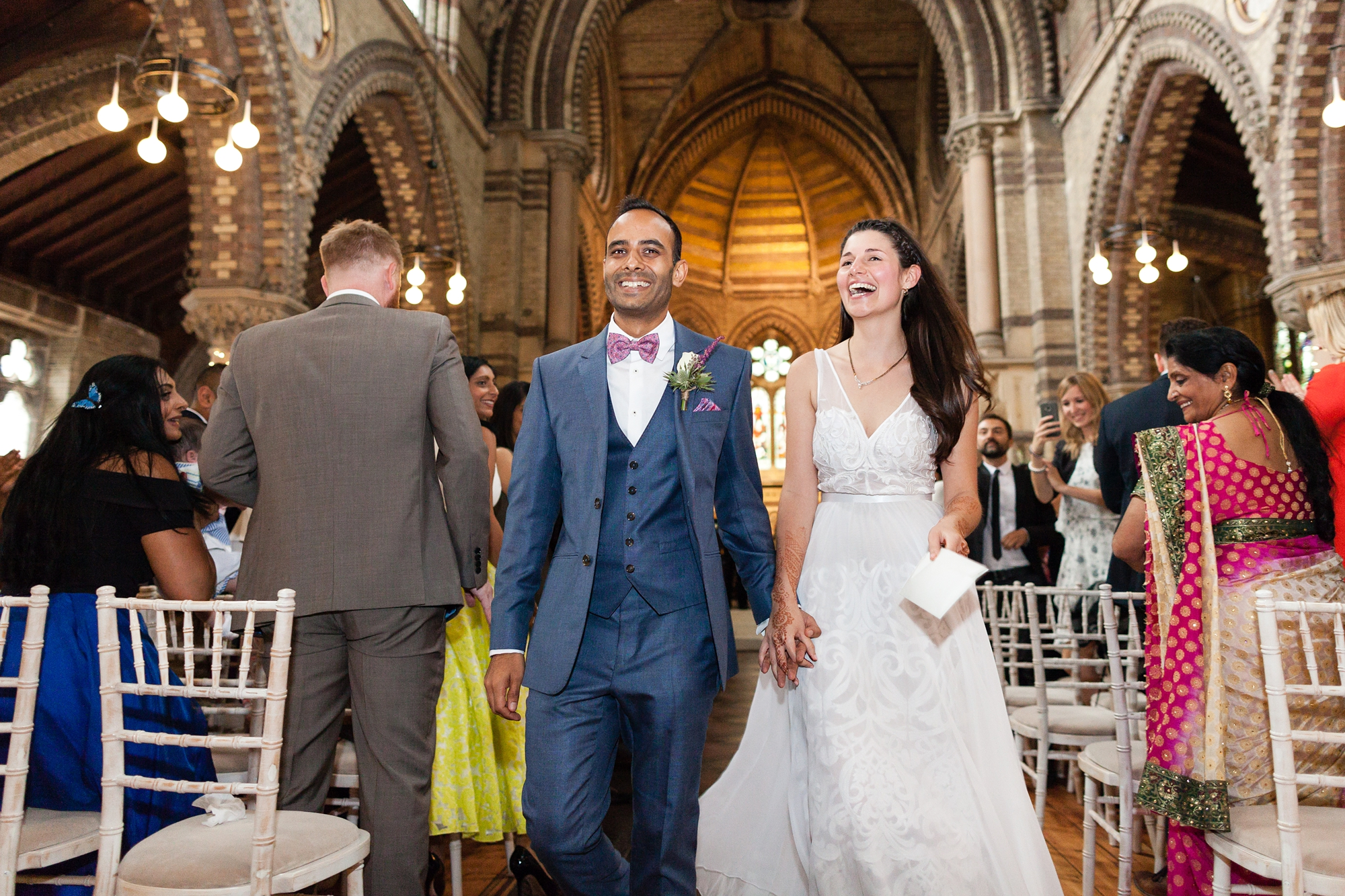 St. Stephens Hampstead Wedding bride and groom walk up aisle smiling and laughing