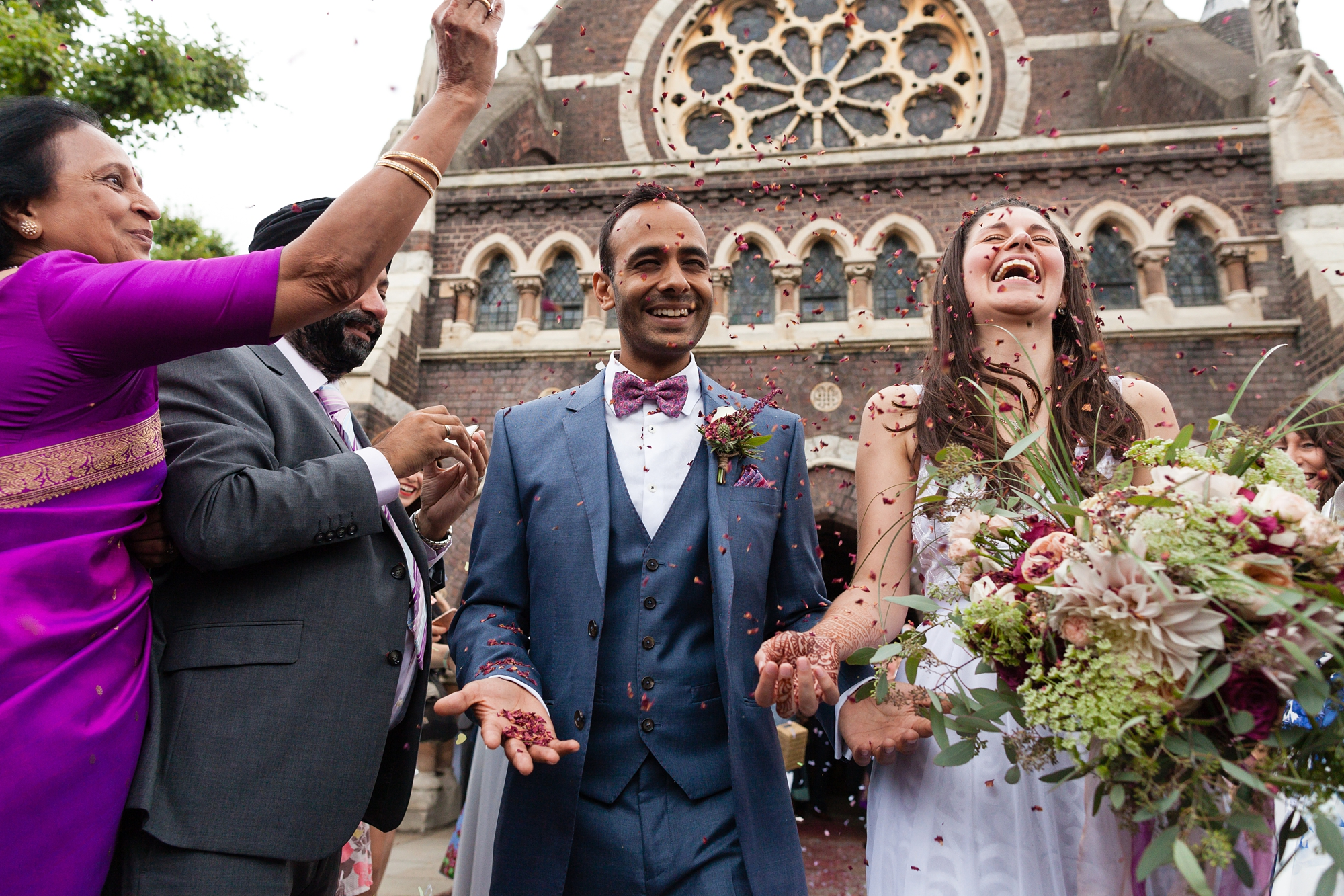 Bride and groom laugh as confetti is thrown St. Stephens Hampstead Wedding