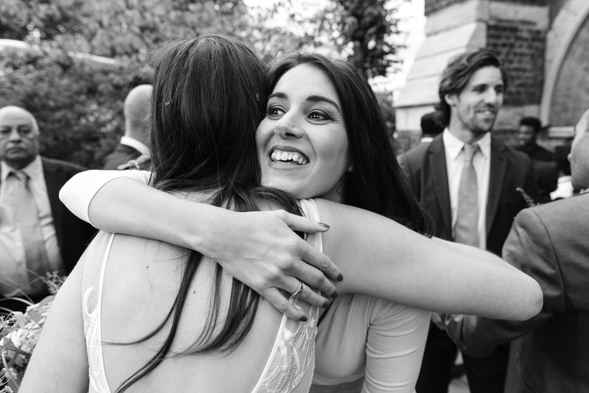 St. Stephens Hampstead Wedding hugging guest after ceremony
