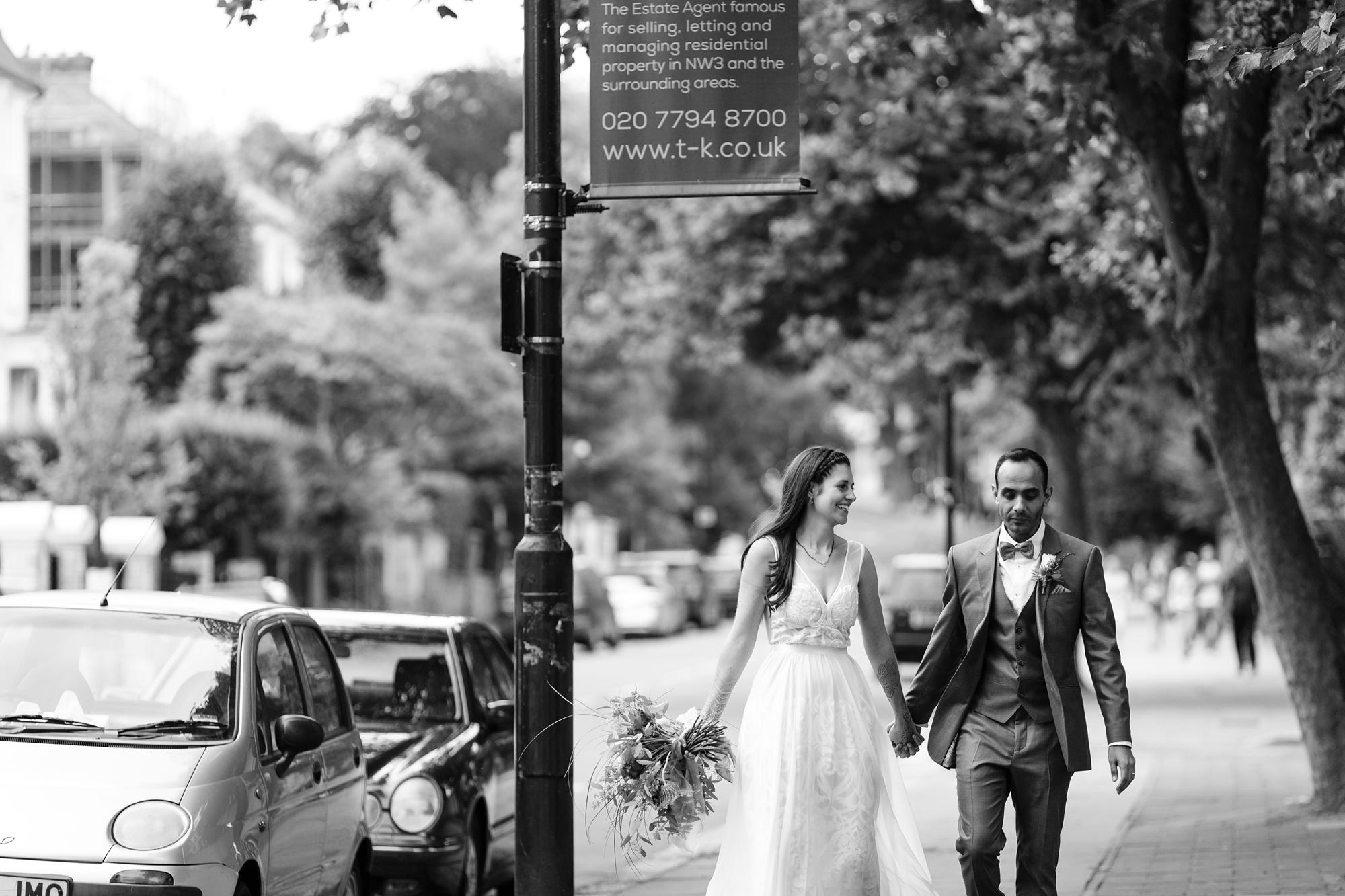 St. Stephens Hampstead Wedding bride and groom walk up the street in Hamstead