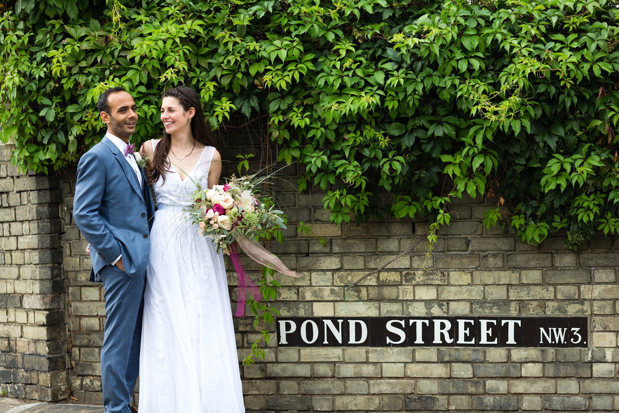 Bride and groom pose in front of pond street sign