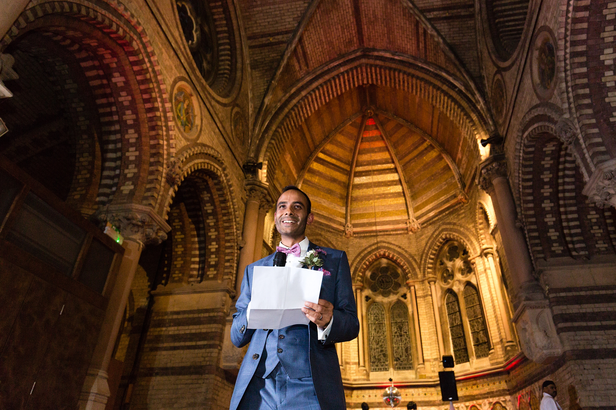 Groom giving speech in front of church backdrop St Stephens Hampstead Wedding Photography